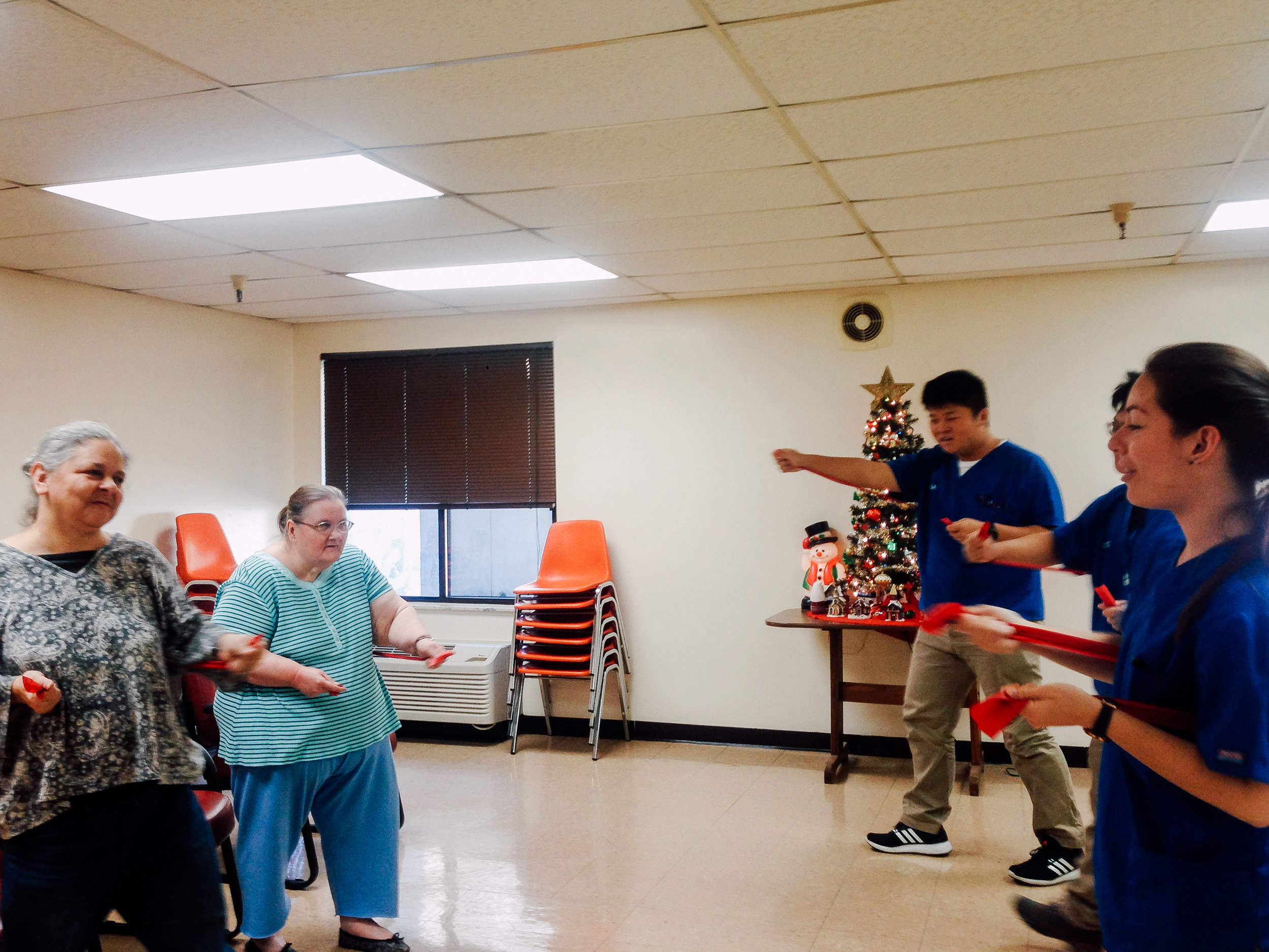At a health fair teaching patients how to do resistance band exercises