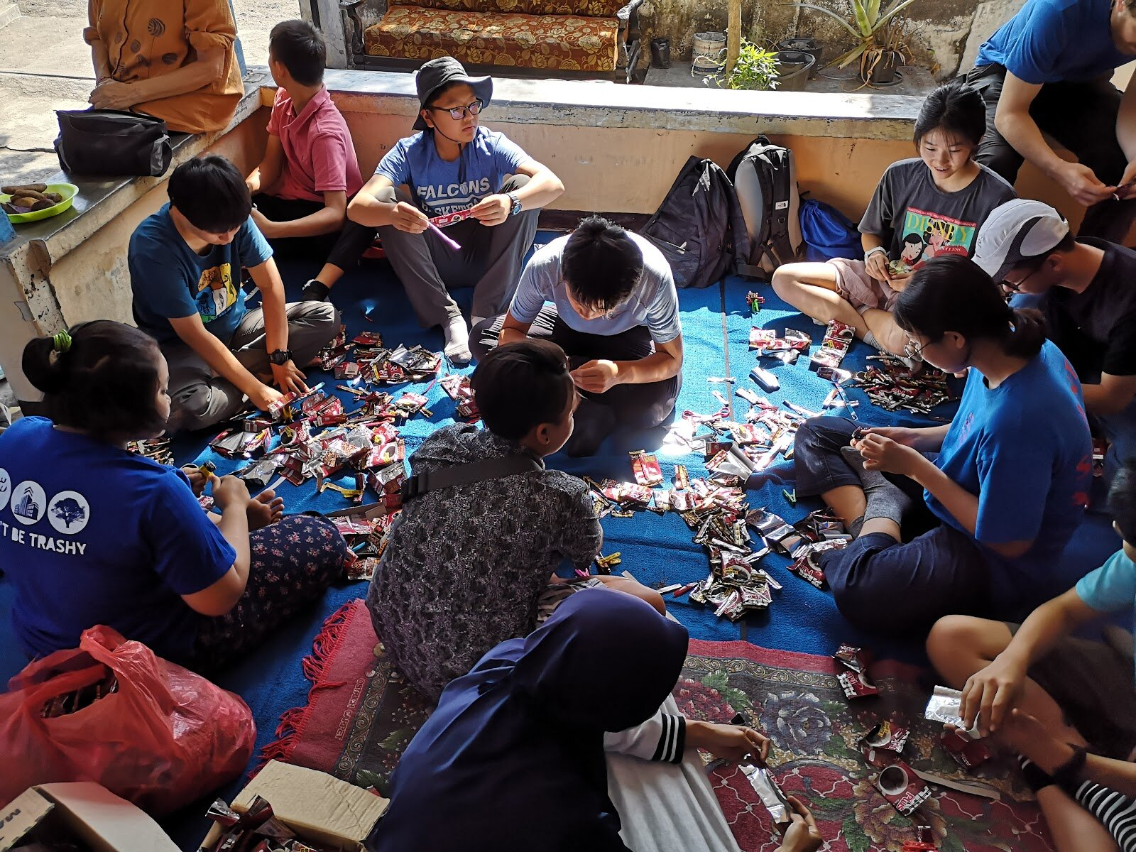 Keystone youths learning the art of weaving plastics into purses and bags as part of the 'Recycling Plastics into Bags' project with Friends of Menjangan.