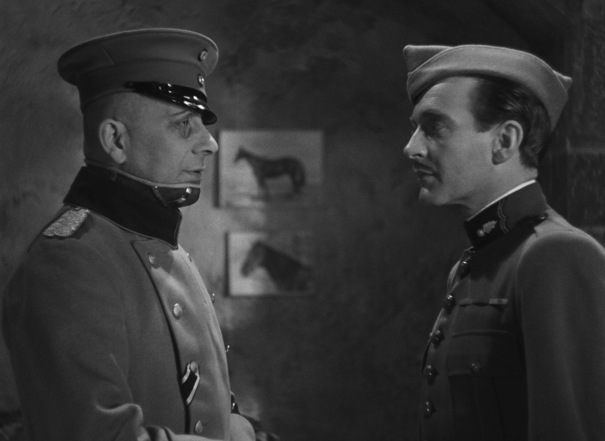 Serving warring flags, but finding amity in their common aristocratic roots, the German Captain von Rauffenstein (Erich von Stroheim) chats with his French prisoner,Captain de Boeldieu (Pierre Fresnay), in Jean Renoir's anti-war drama, The Grand Illusion .