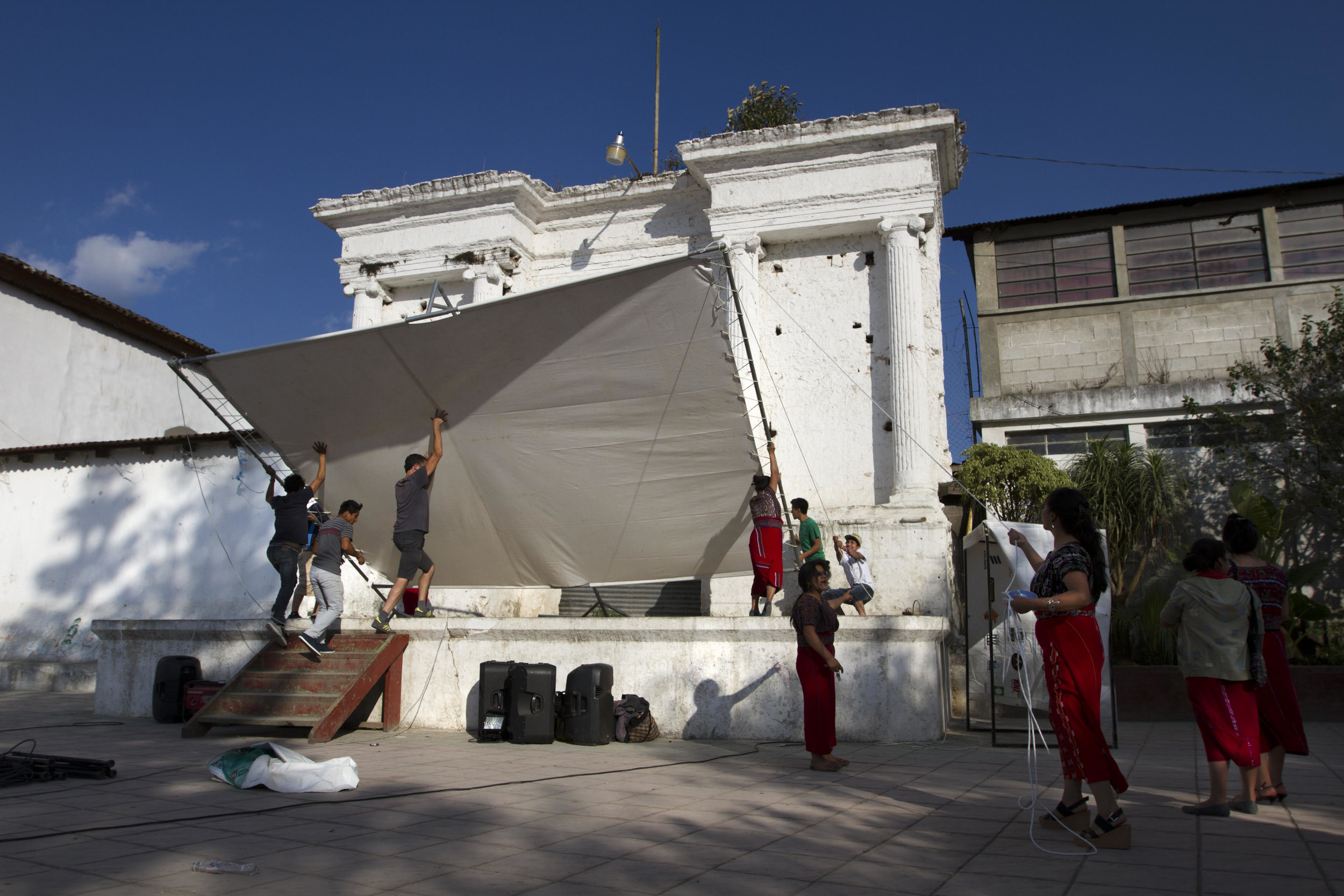 Putting  up the outdoor screen for the premiere of  Granito: How to Nail a Dictator  in Nebaj, Guatemala. The film was translated into Mayan Ixil by a translation team and recorded in the local radio station. The Mayan Ixiles were a target of General Ríos Montt's genocide in 1982. Photo by James Rodríguez.