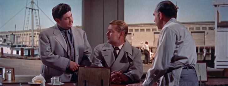 El pesado de Amato, Hammy (Stanley Adams), le da al inquisitivo Rollins una pista de mano dura para despedir.