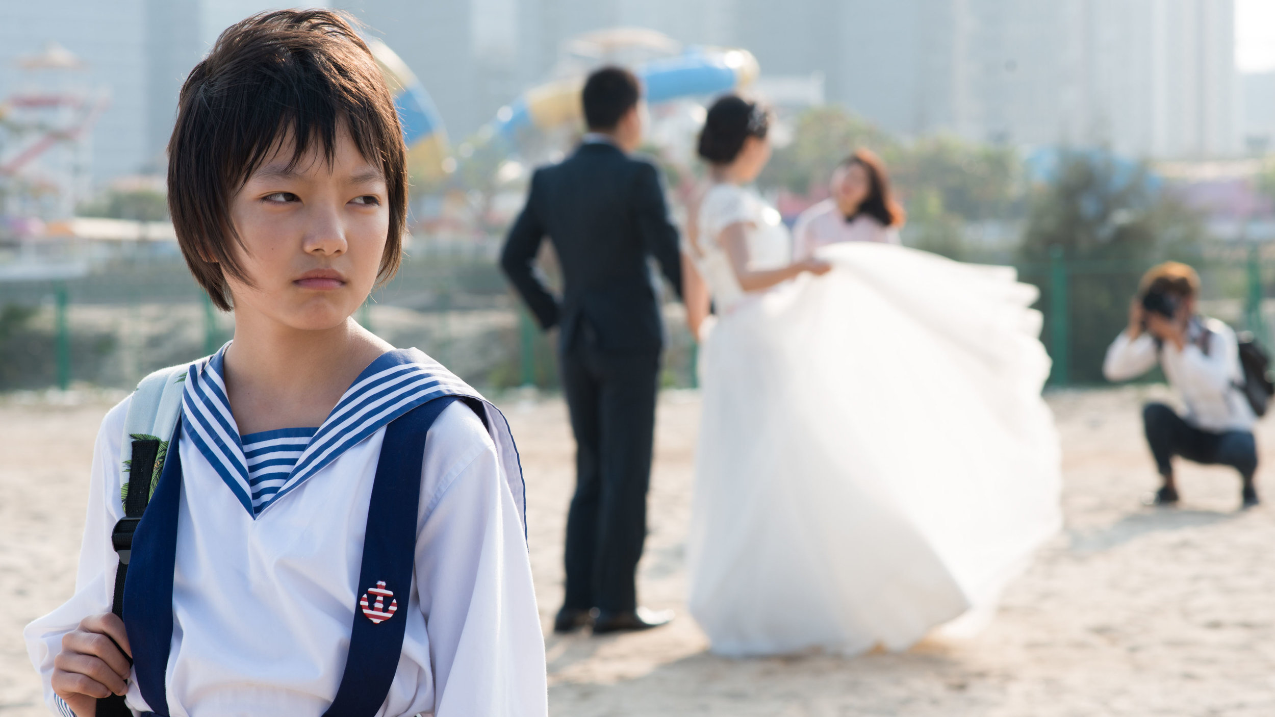 Traumatized Wen (Meijun Zhou) surrounded by happy tourists taking romantic wedding pictures on the beach.