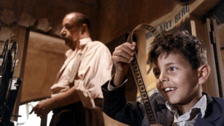Young Salvatore Di Vita (Salvatore Cascio) learns about the magic of movies from Alfredo (Philippe Noiret), the projectionist at the  Cinema Paradiso.