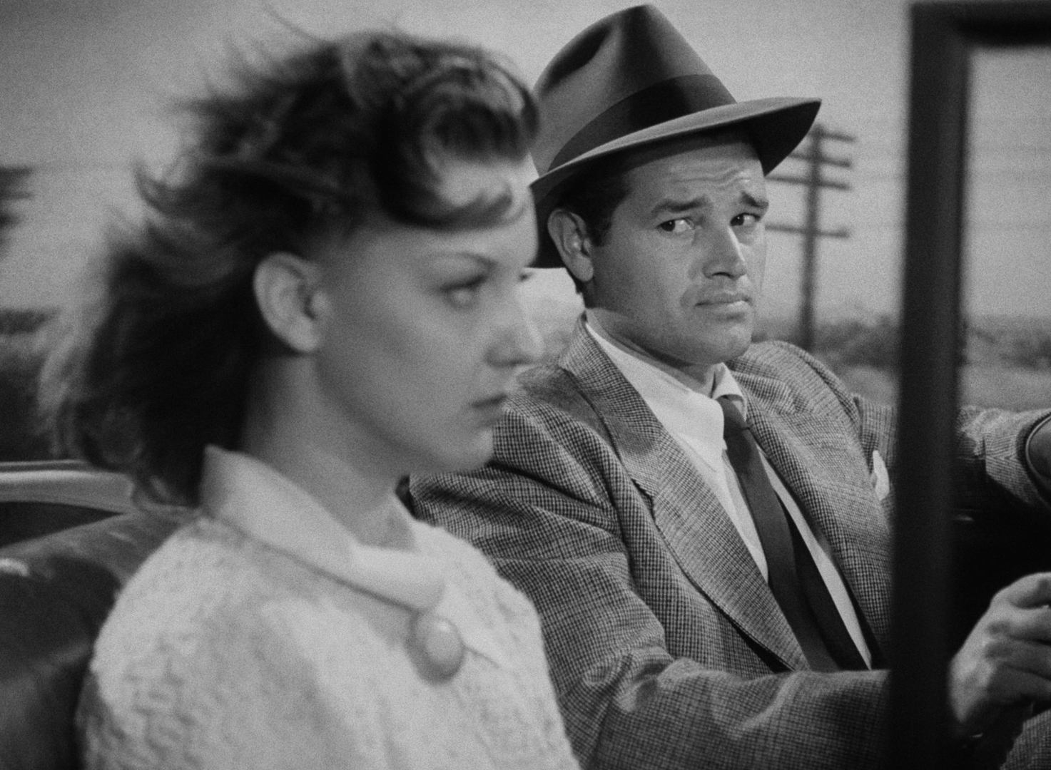 Al almost immediately regrets offering a ride to hitchhiker Vera (Ann Savage), who lets him know she is fully aware that the car does not belong to Al.