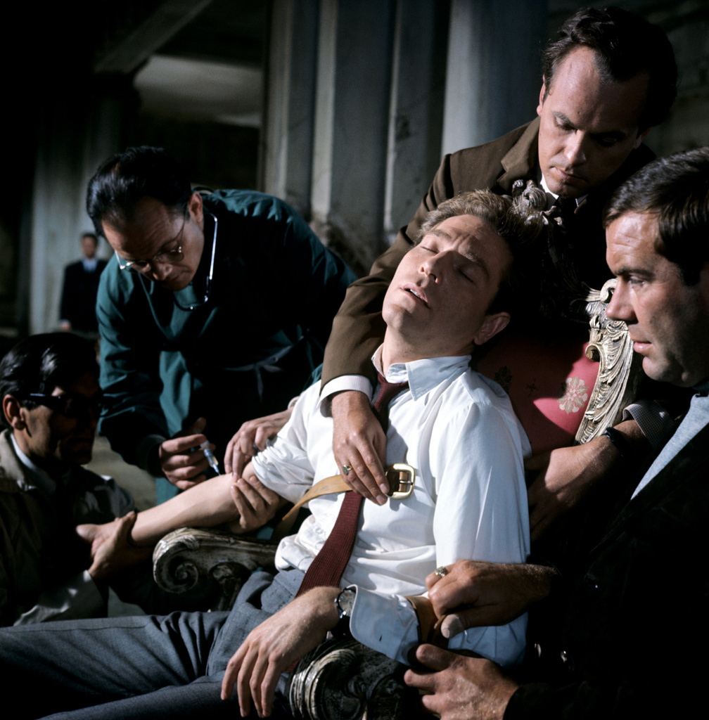 Quiller being injected with truth serum by agents of Phoenix.