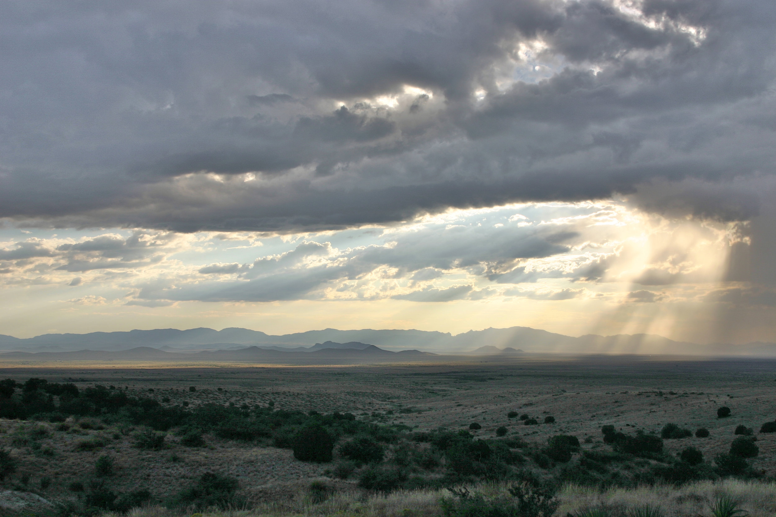 VIEW ACROSS RIGGS FAMILY RANCH LAND LOOKING WEST TO THE PAT HILLS AND DRAGOON MOUNTAINS FROM THE FOOTHILLS OF THE CHIRICAHUA MOUNTAINS