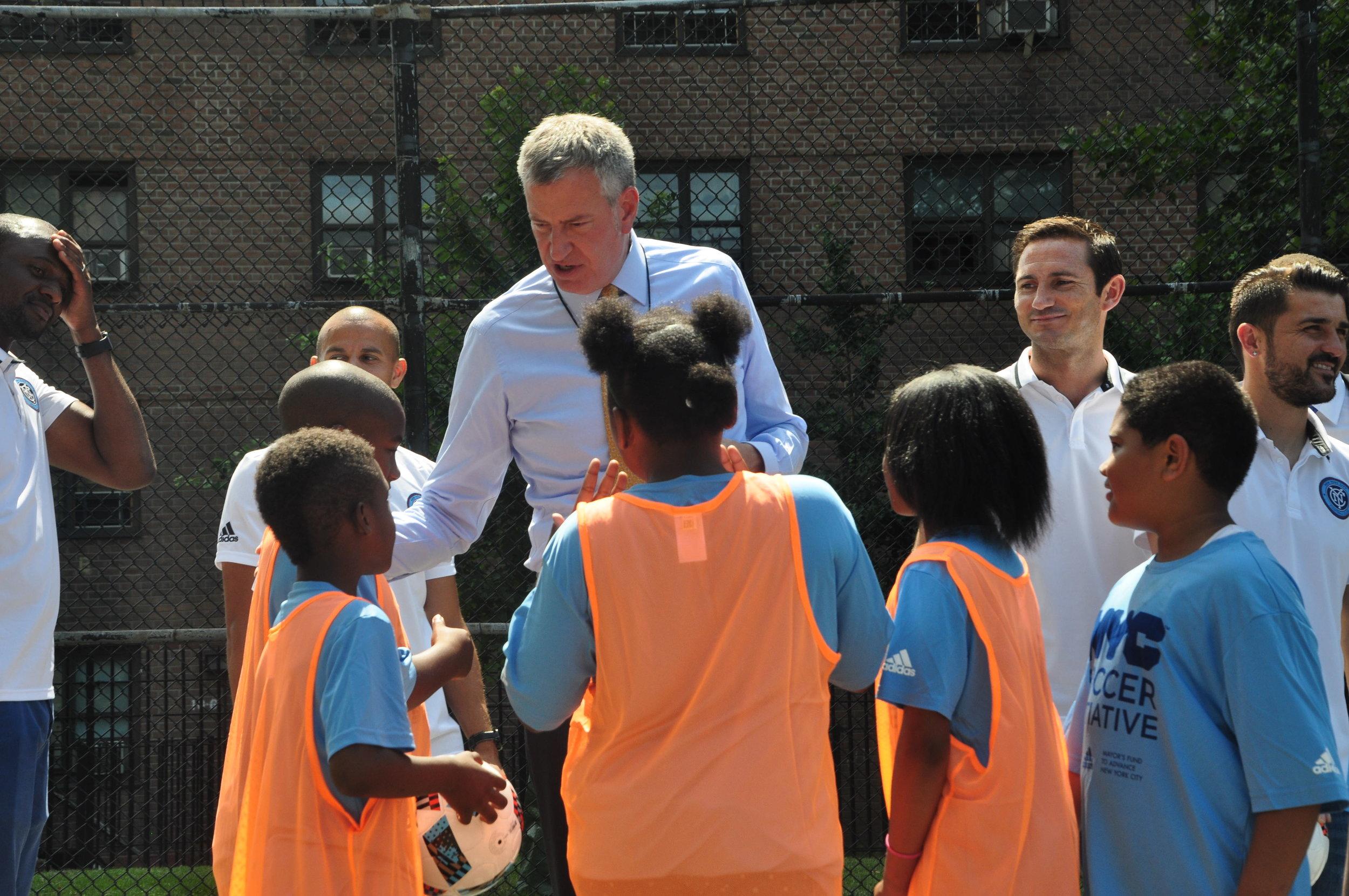 by Samali Bikangaga. Mayor de Blasio huddles with Bronx kids at Mill Brook Houses on July 11.