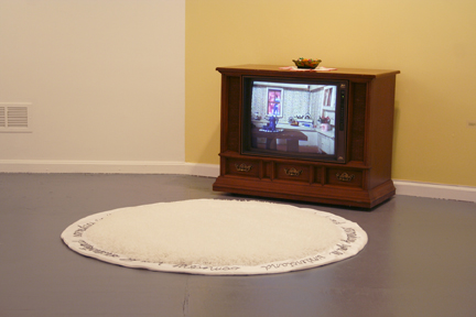 "I Don't Love You Anymore  console television, shag rug with hand embroided ""someday you'll understand"", satin fabric, ribbon candy, candy dish, dvd: 2.39 minutes  from:  It's Not You, It's Me  IA&A Hillyer Art Space, Washington, DC January 12 - February 16, 2007"