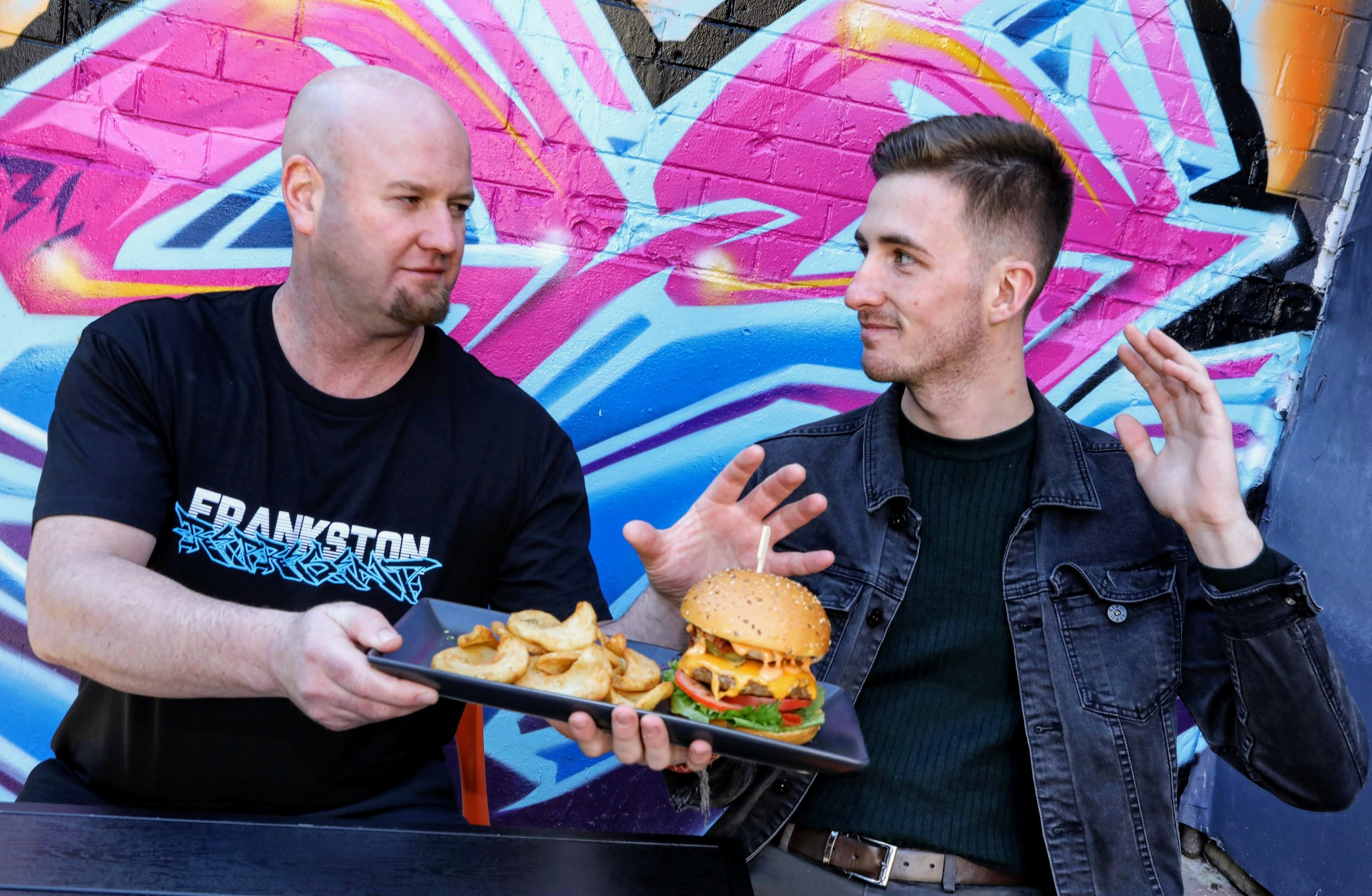 Frankston Mayor Michael O'Reilly serves Youth Mayor Aaron Quarrell a burger during Frankston City Council's Burger Off competition. Photo by Steve Brown
