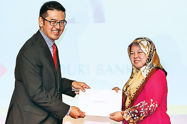 JA Brunei's Managing Director Louis Tan (L) presenting the certificate of appreciation to a representative of one of the participating schools
