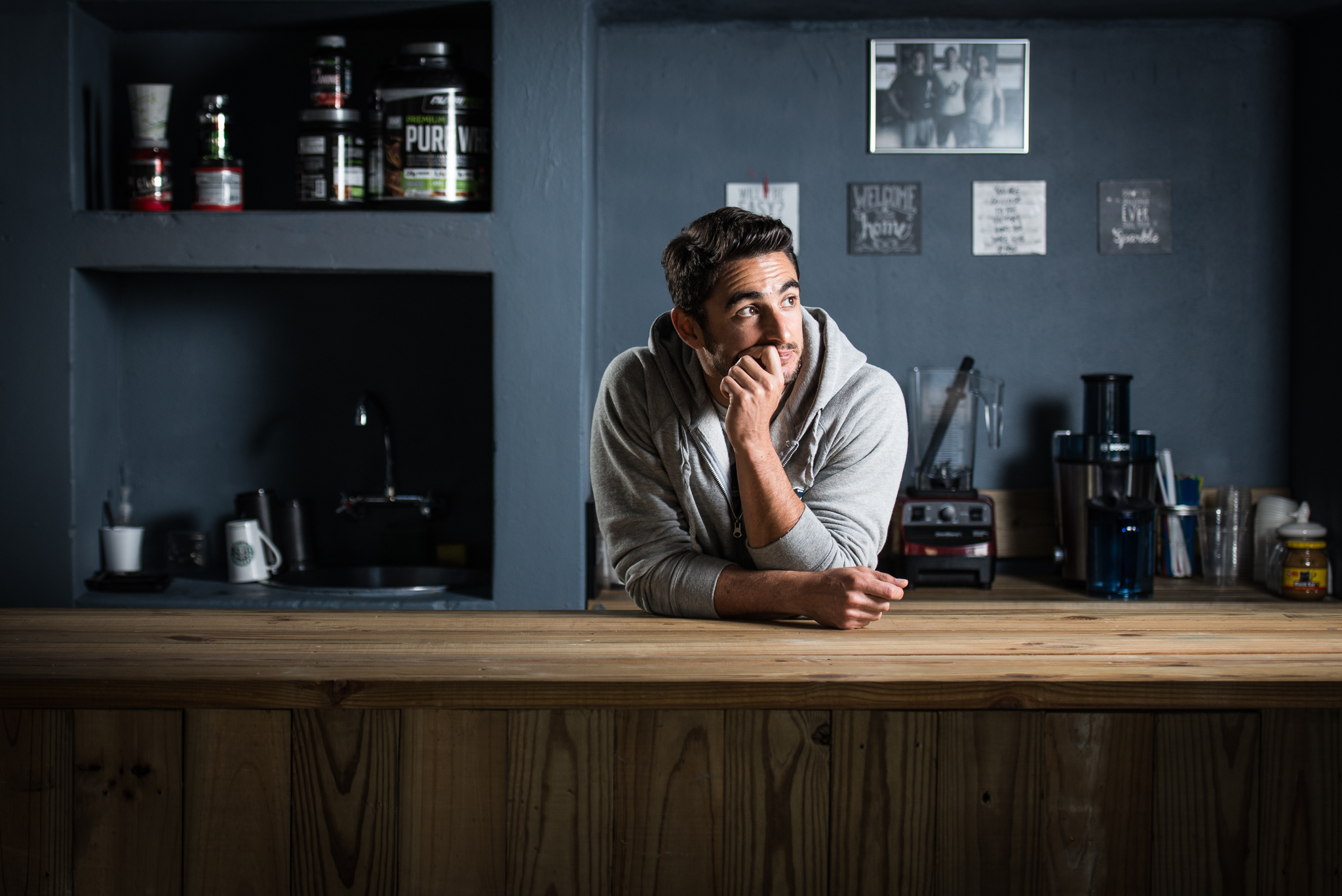 Josh, standing at the bar he built, in the gym he opened.