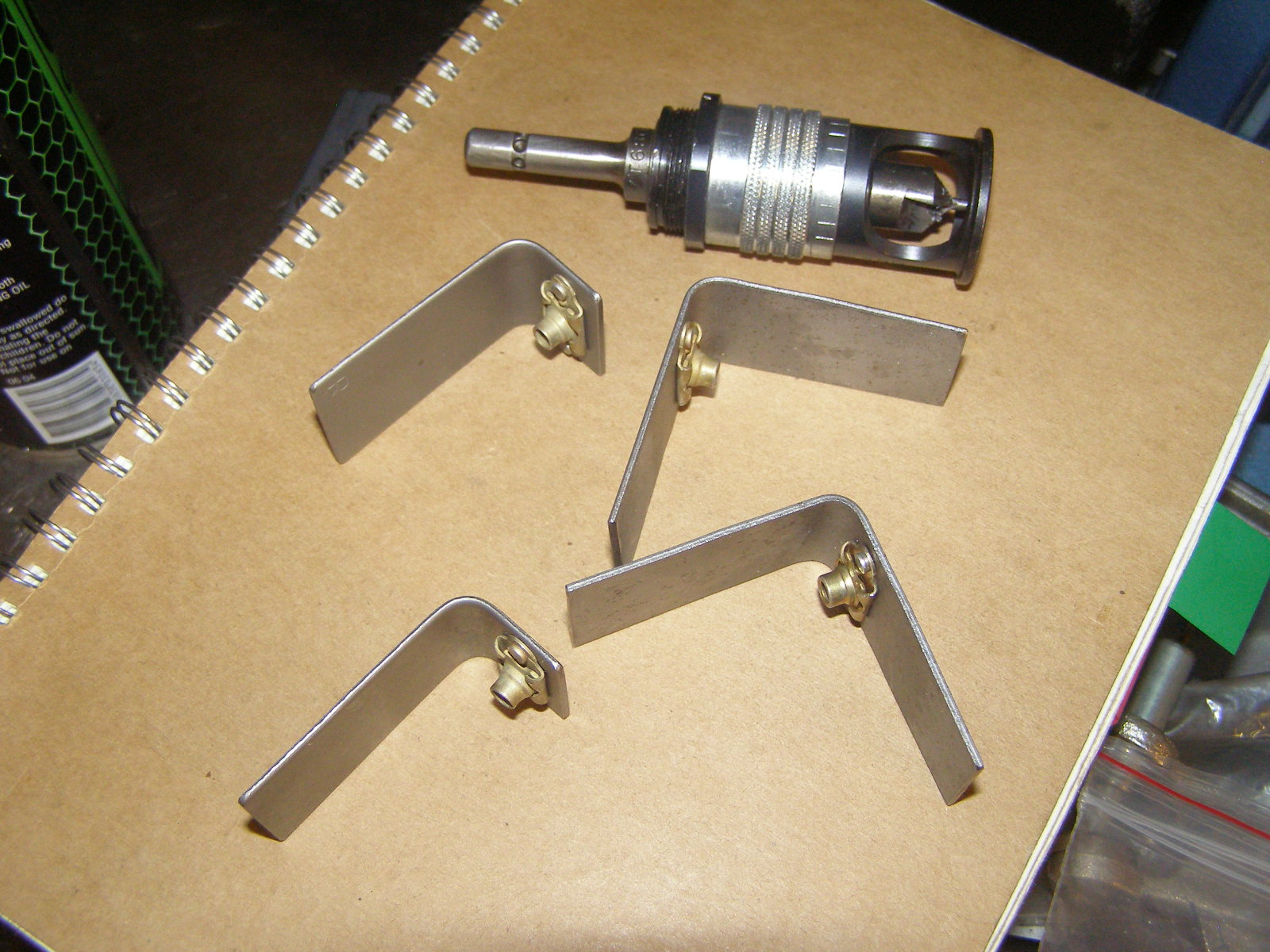 Windage tray attach brackets manufactured and fitted with floating and self-locking anchor nuts waiting to be welded to sump interior.  Microstop countersink tool in background used to countersink brackets to accept anchor nut attach rivets.