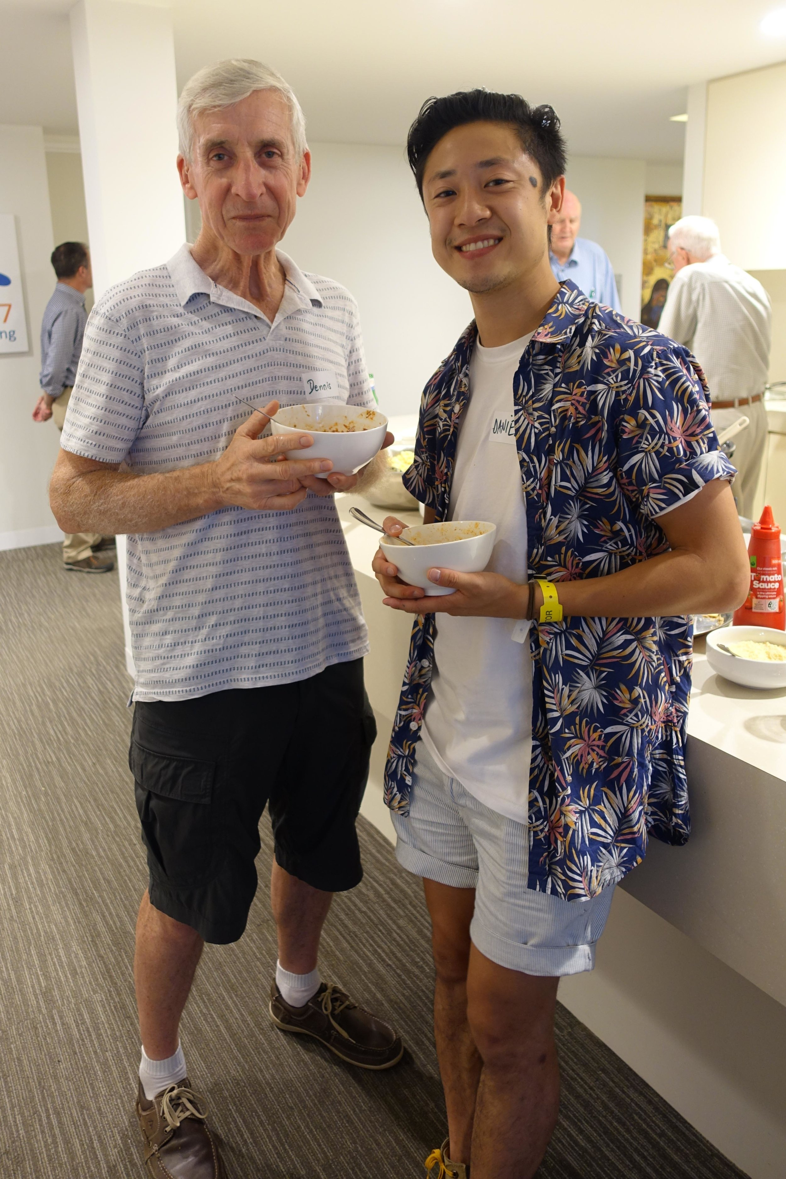 Br Dennis Cooper and Daniel Nguyen chatting over a bowl of pasta