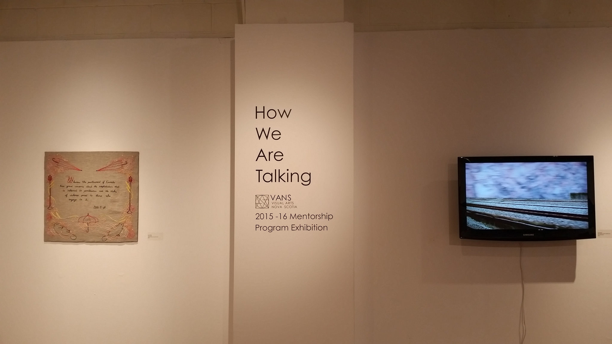 Left: Anna Taylor,  Moral Code  (cotton thread on linen, 26″ x 24″) and right, Becka Barker,  Place Holder II: 110/300 km/hr  (digital video, 1920x1080). Installation shot from How We Are Talking, VANS 2015-2016 Mentorship Program Exhibition.