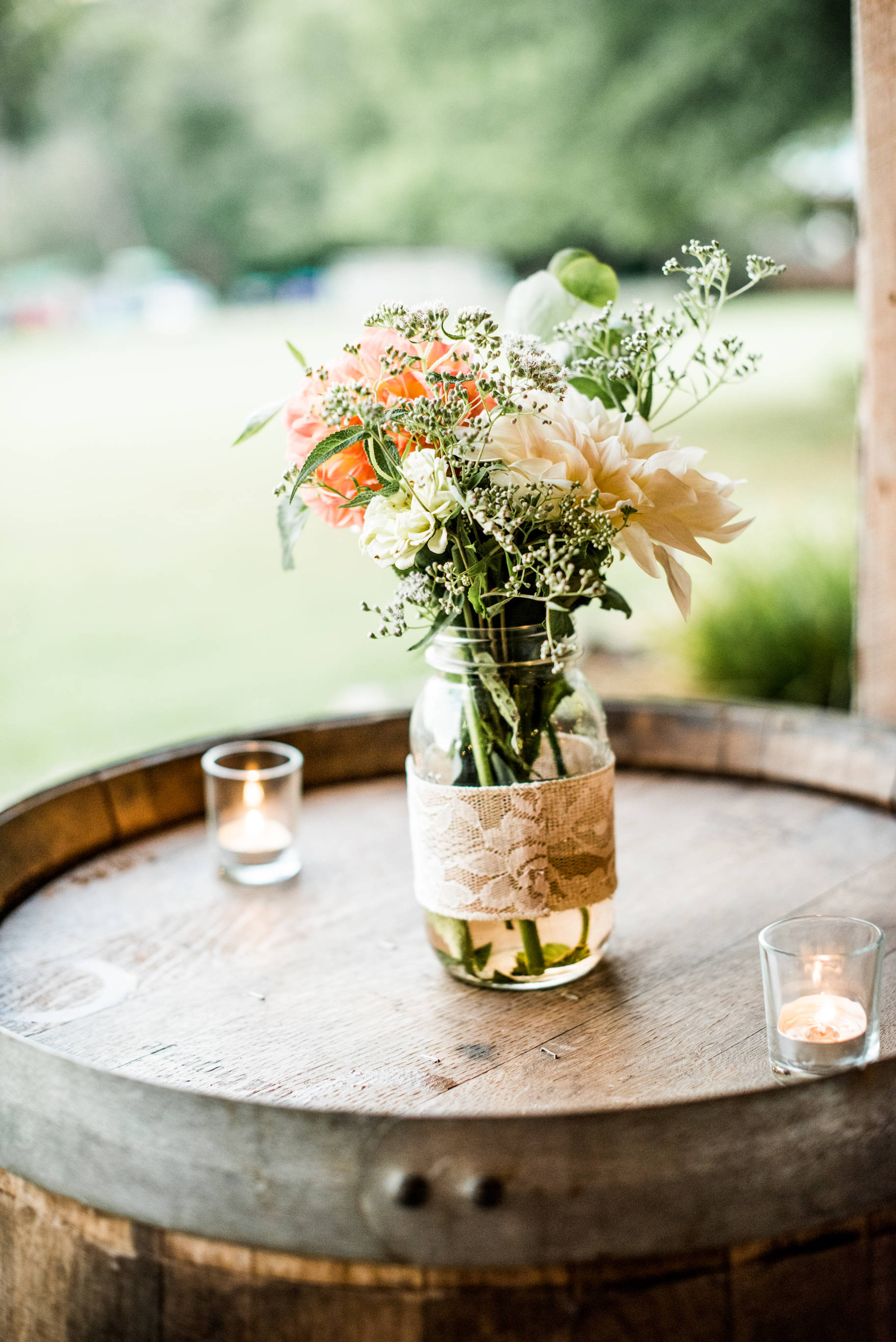 romantic and rustic flowers on barrel with candles at wilderness adventure