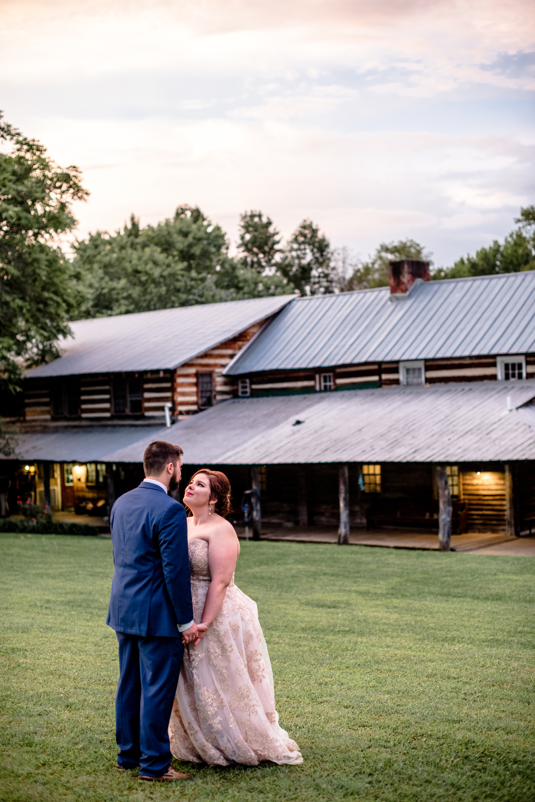 bride and groom hold hands romantically by lodge cabin golden hour susnet