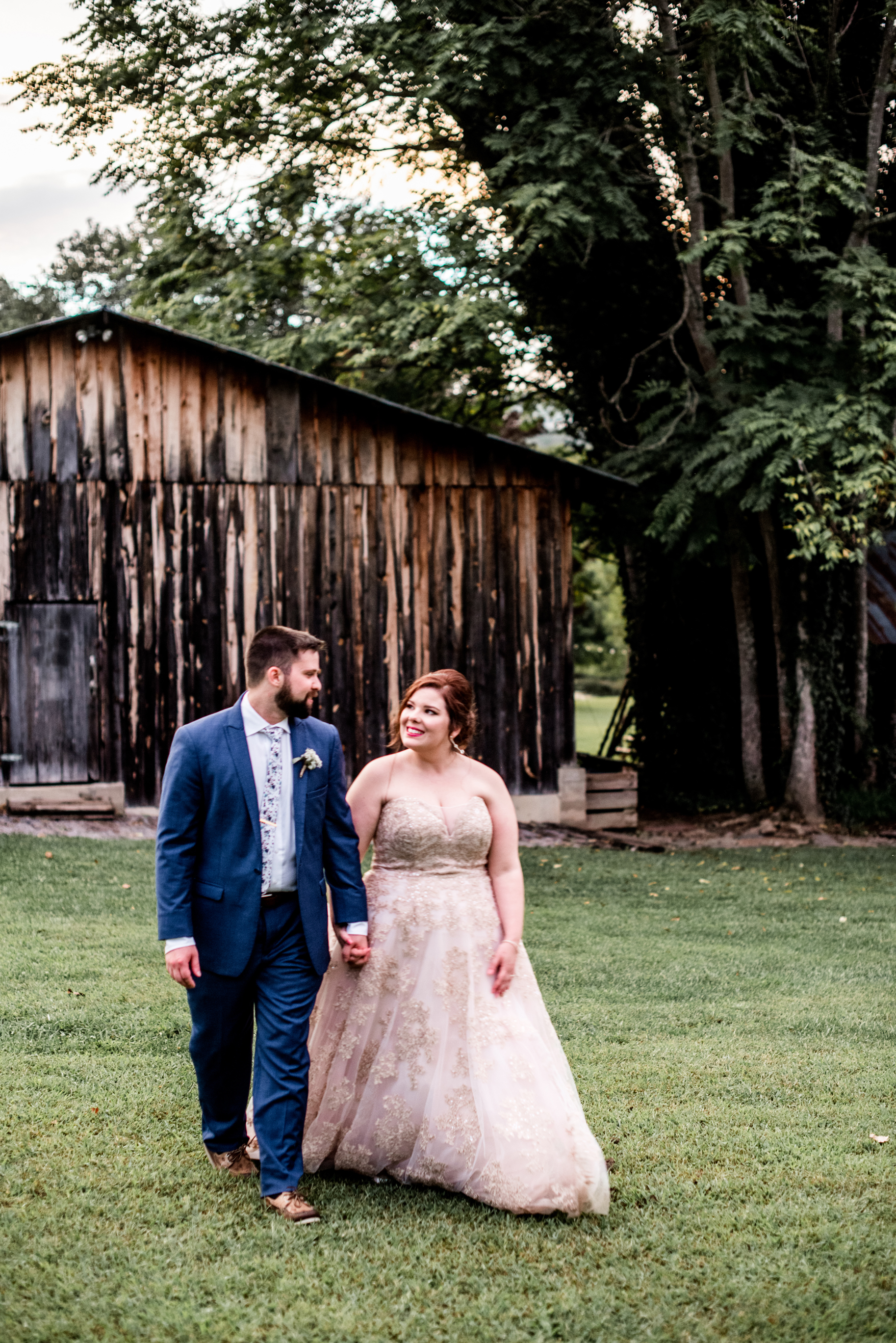 bride and groom stroll holding hands by barn golden hour sunset