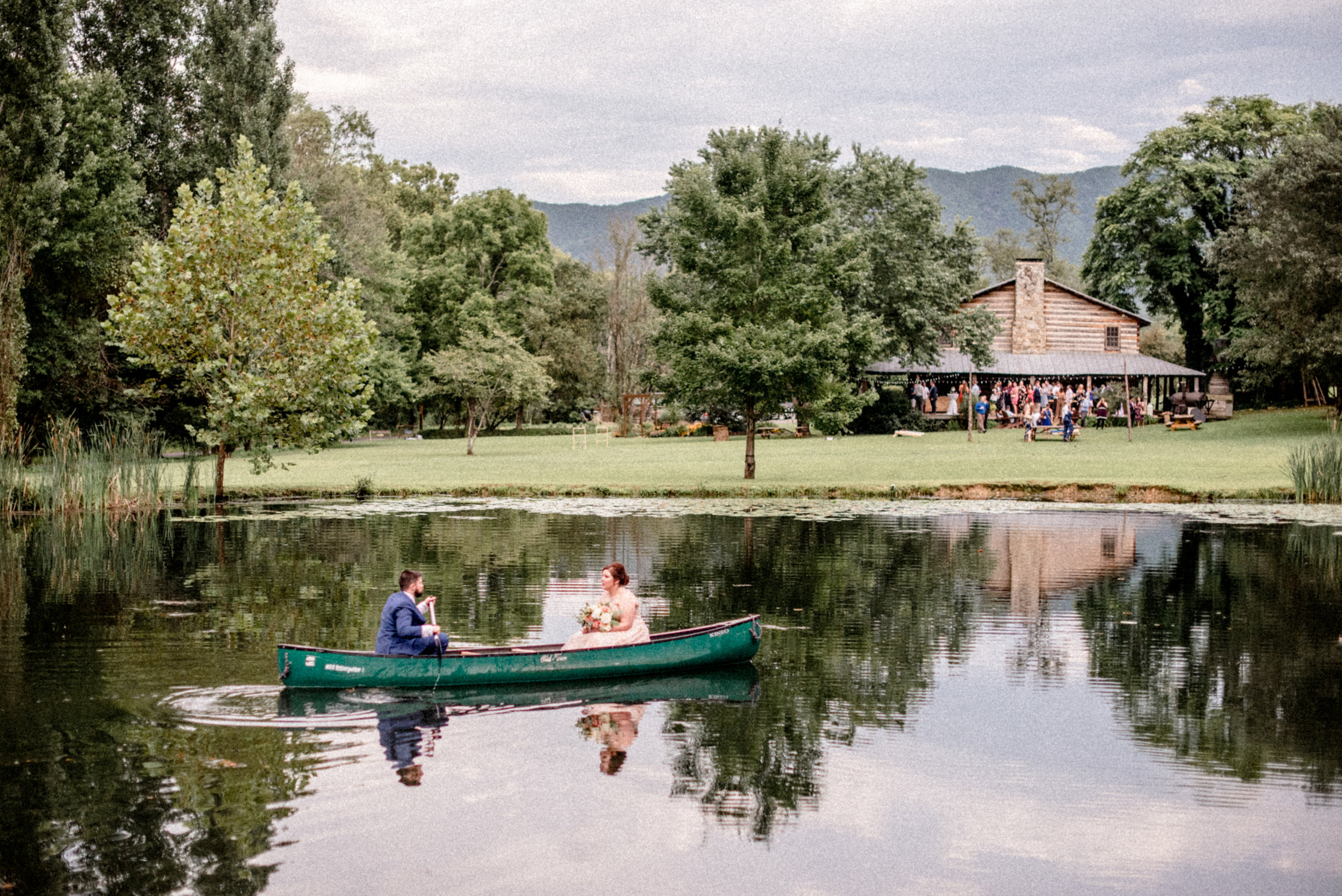 bride and groom romantically canoe on pond at wilderness adventure
