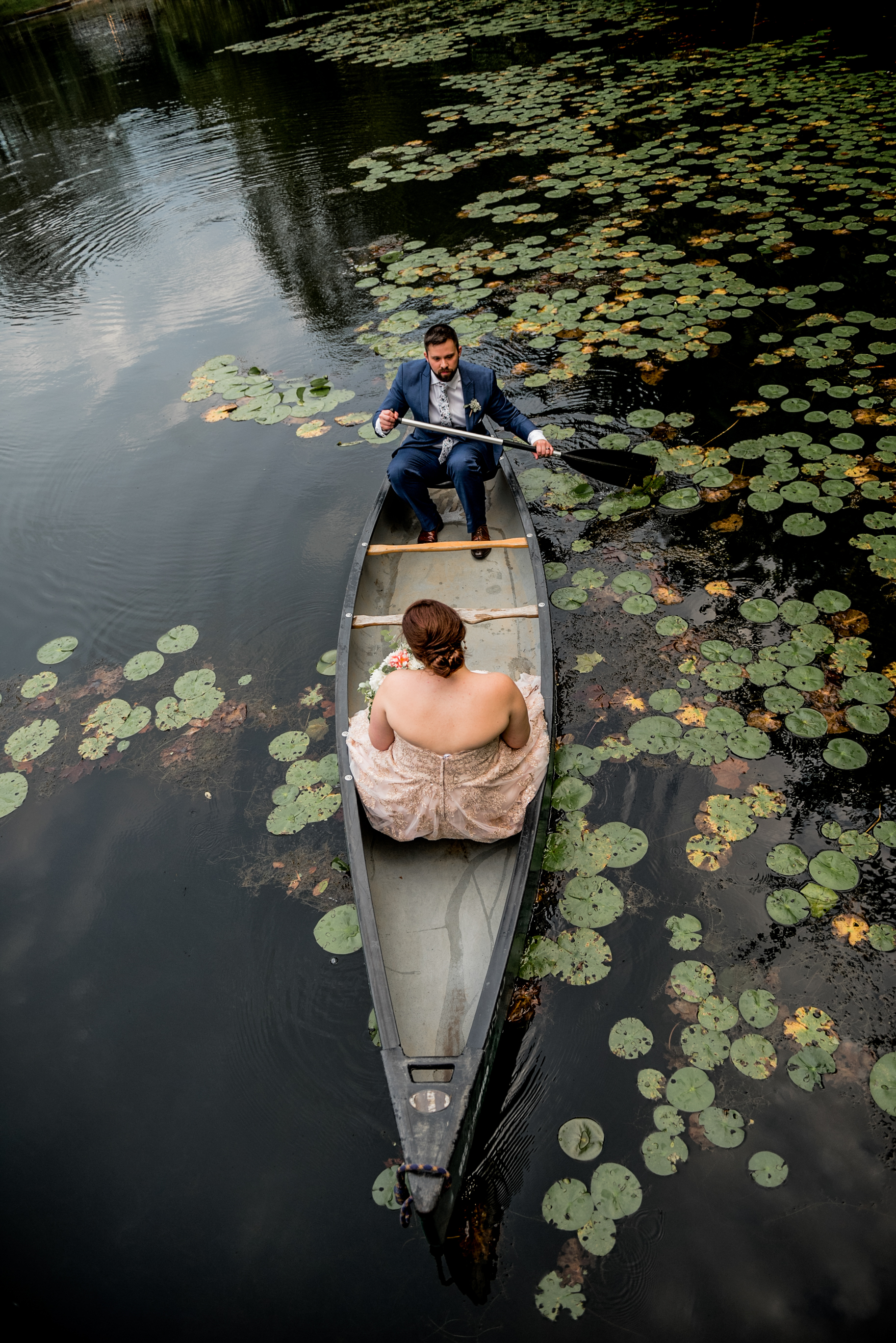bride and groom romantically canoe on pond surrounded by water lilies