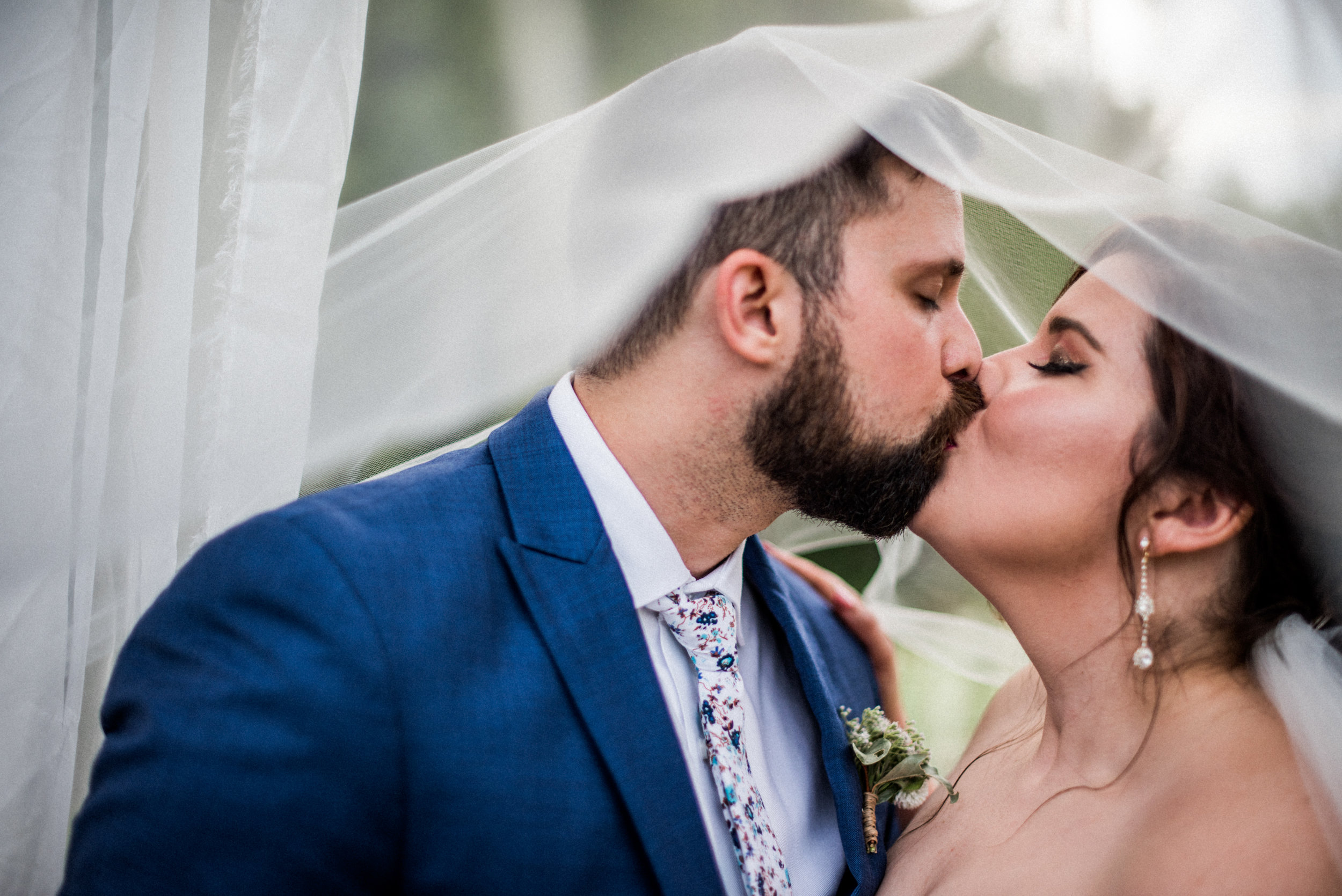 bride and groom kiss under romantic veil