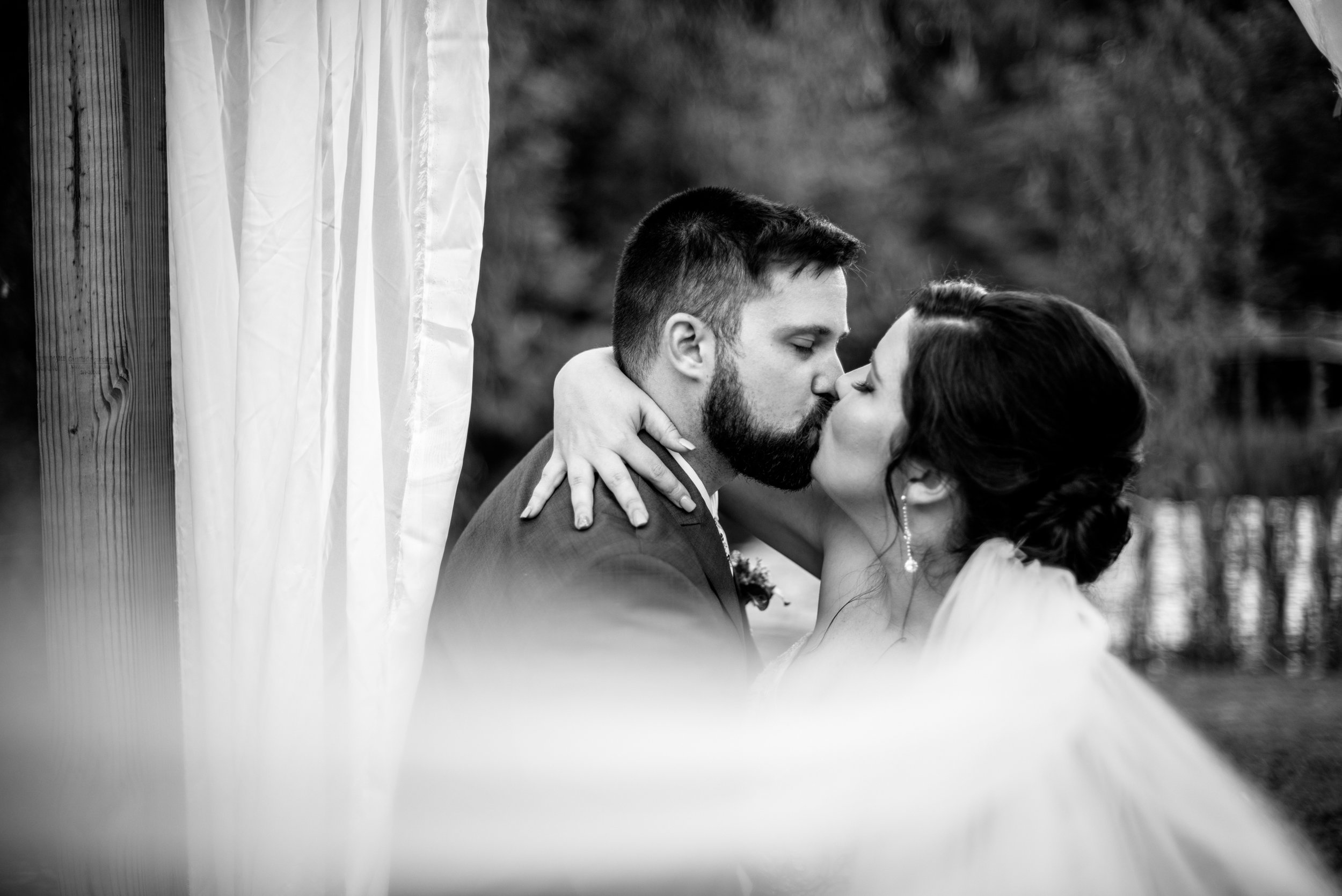 bride and groom kiss with romantic veil black & white