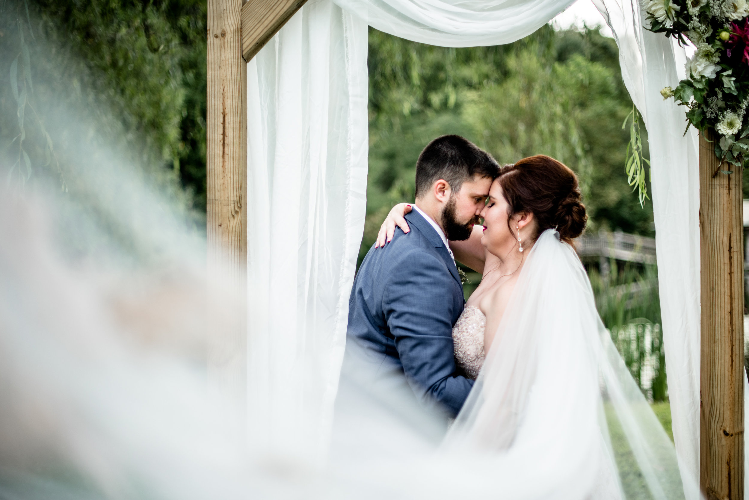 bride and groom embrace with romantic veil