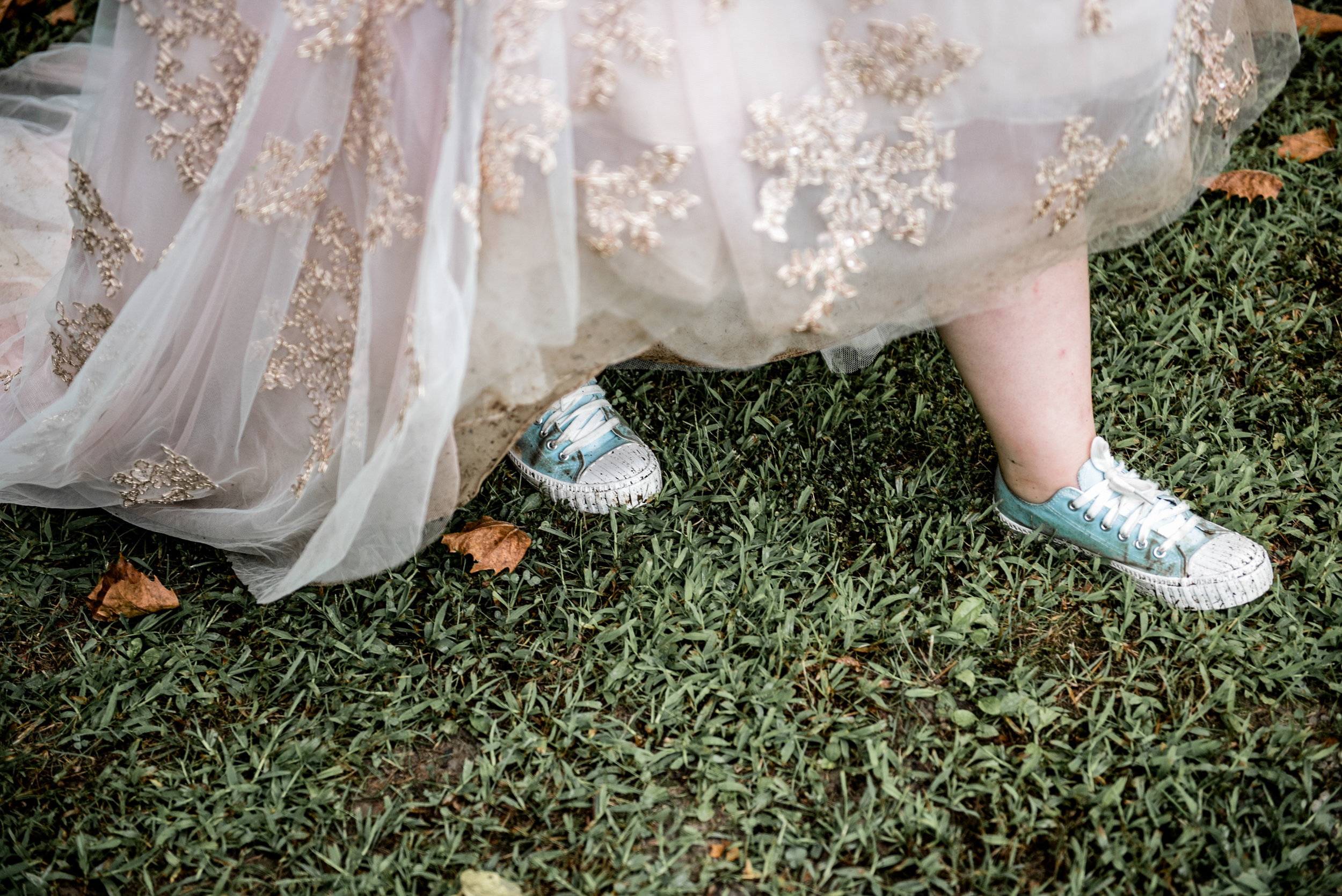 bride strolls across wet grass wearing sneakers and wedding gown