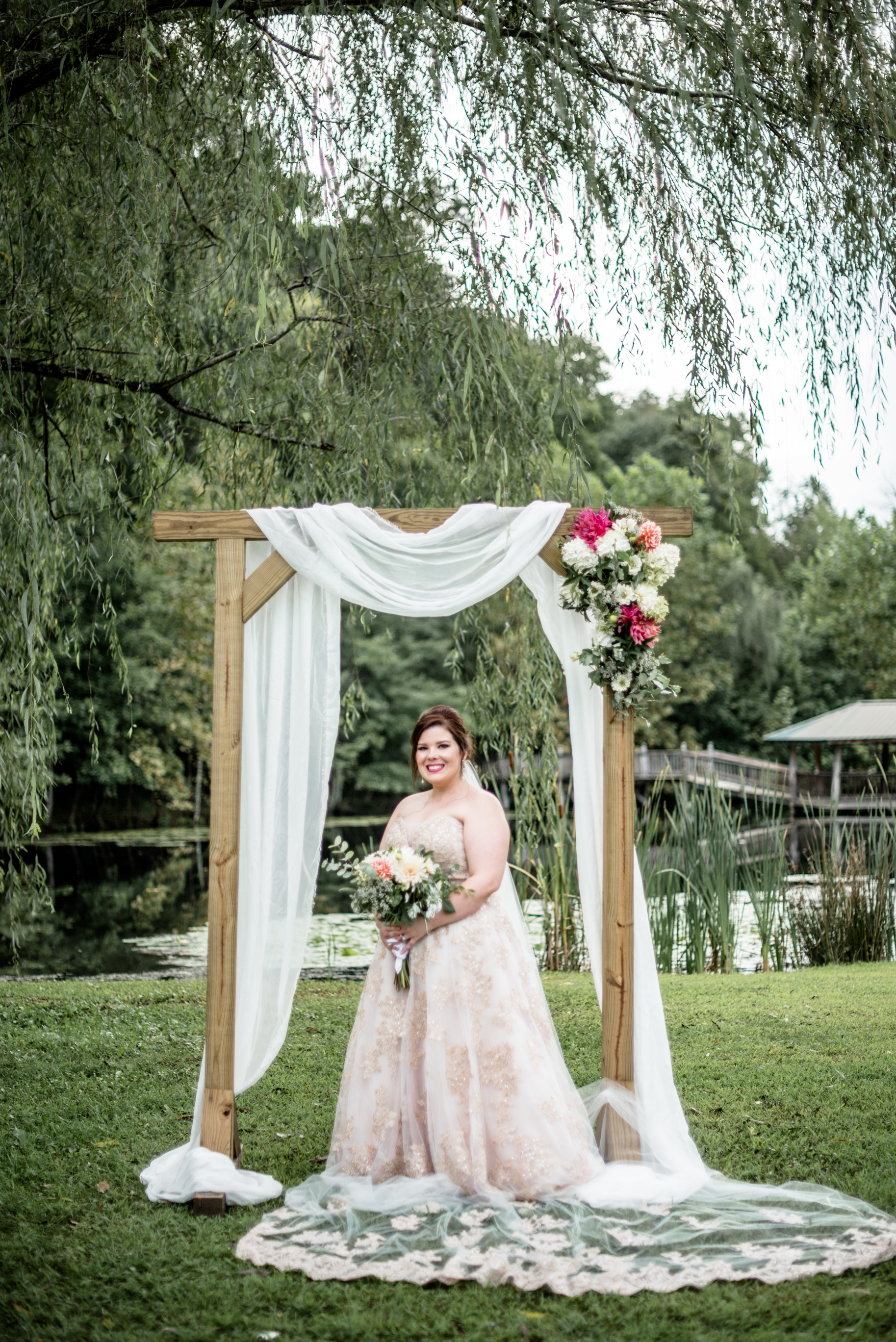 romantic bridal portrait under arbor at willow tree by pond