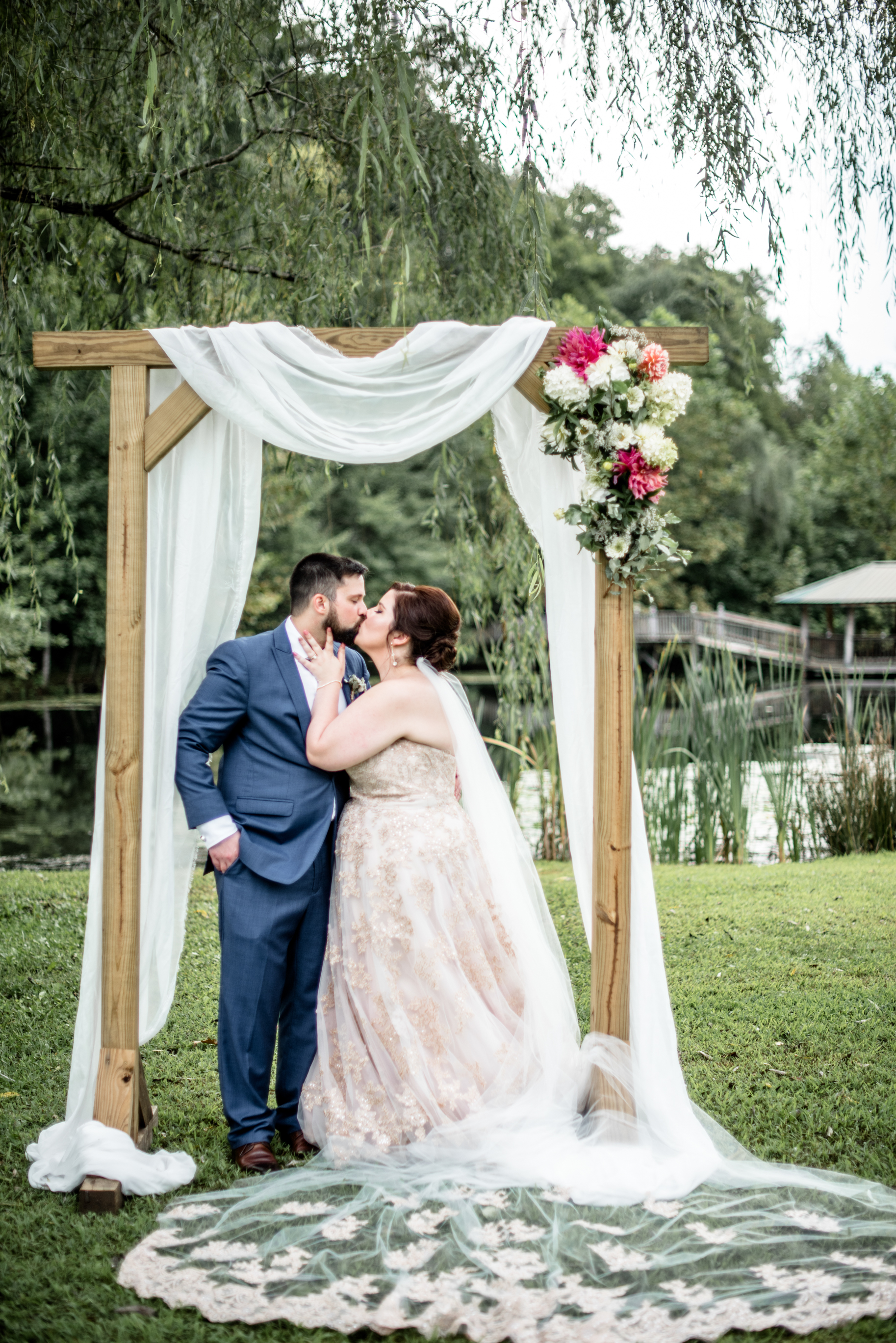 romantic bride and groom kiss under arbor at the willow tree by the pond