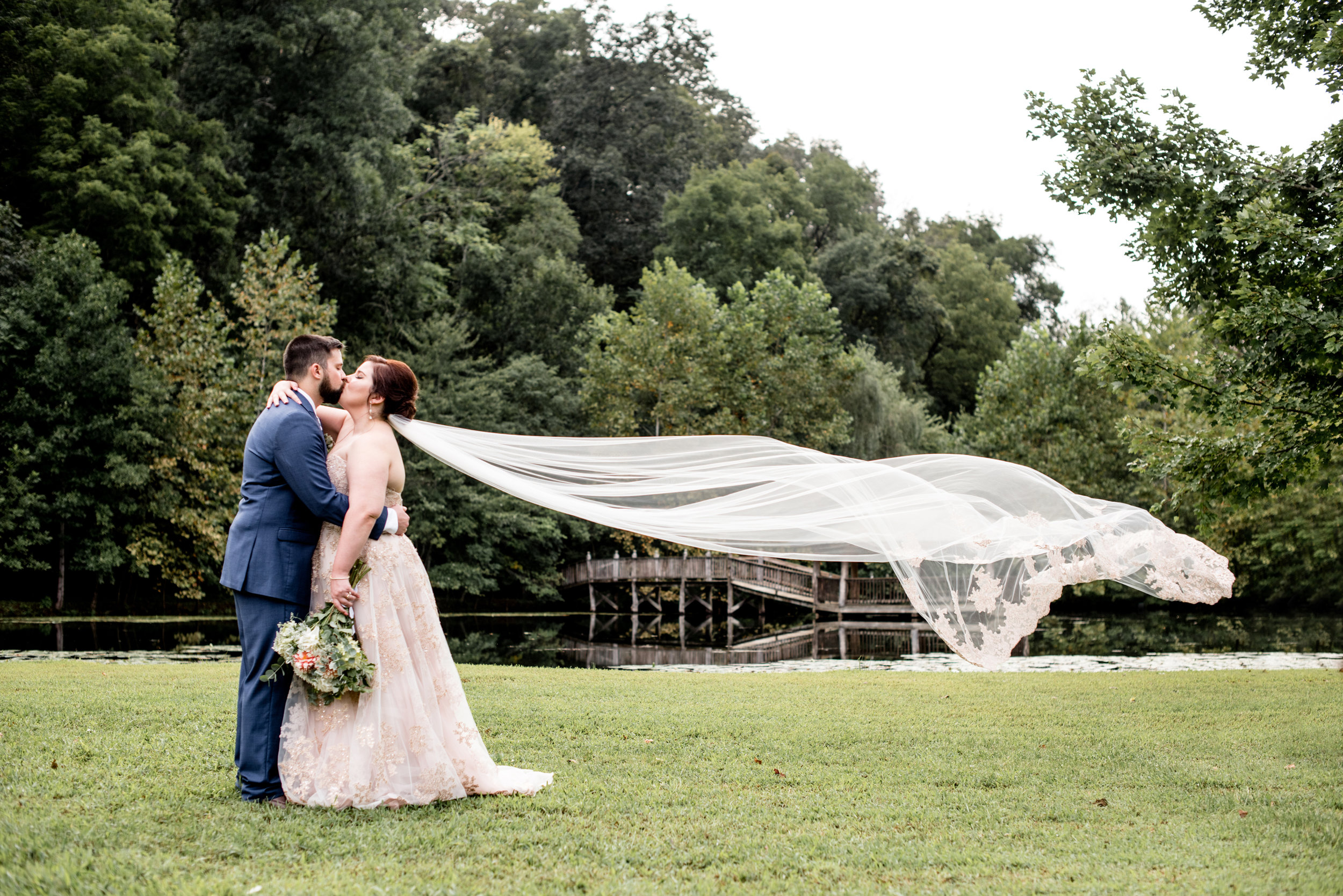 cathedral veil blows in the wind as bride and groom embrace at wilderness adventure