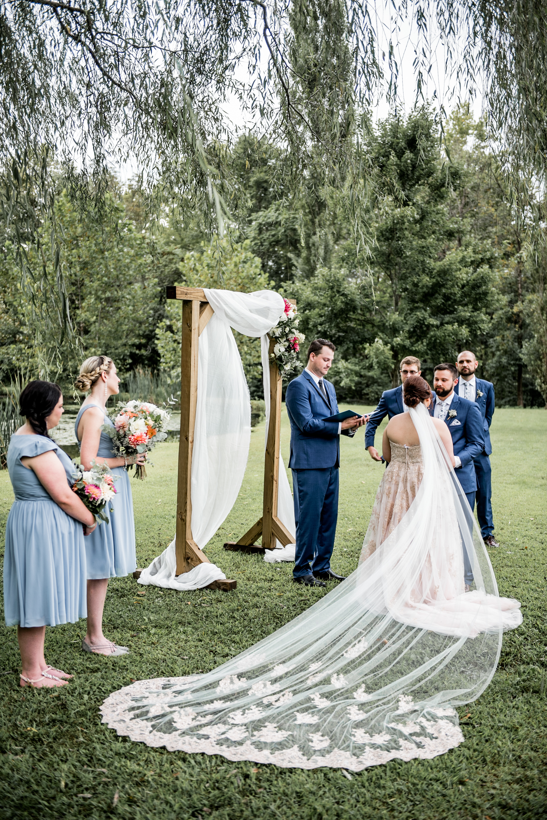 romantic cathedral veil blows in wind during ceremony under willow tree