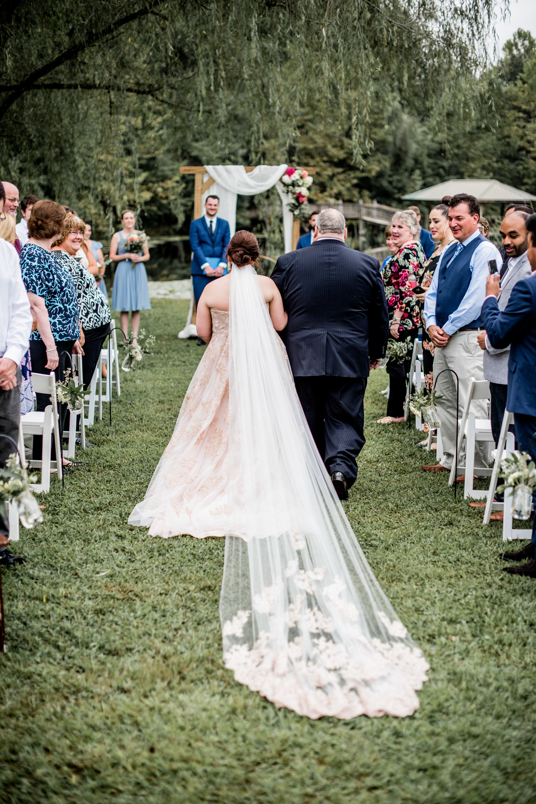 bride and father walk down aisle with romantic cathedral veil
