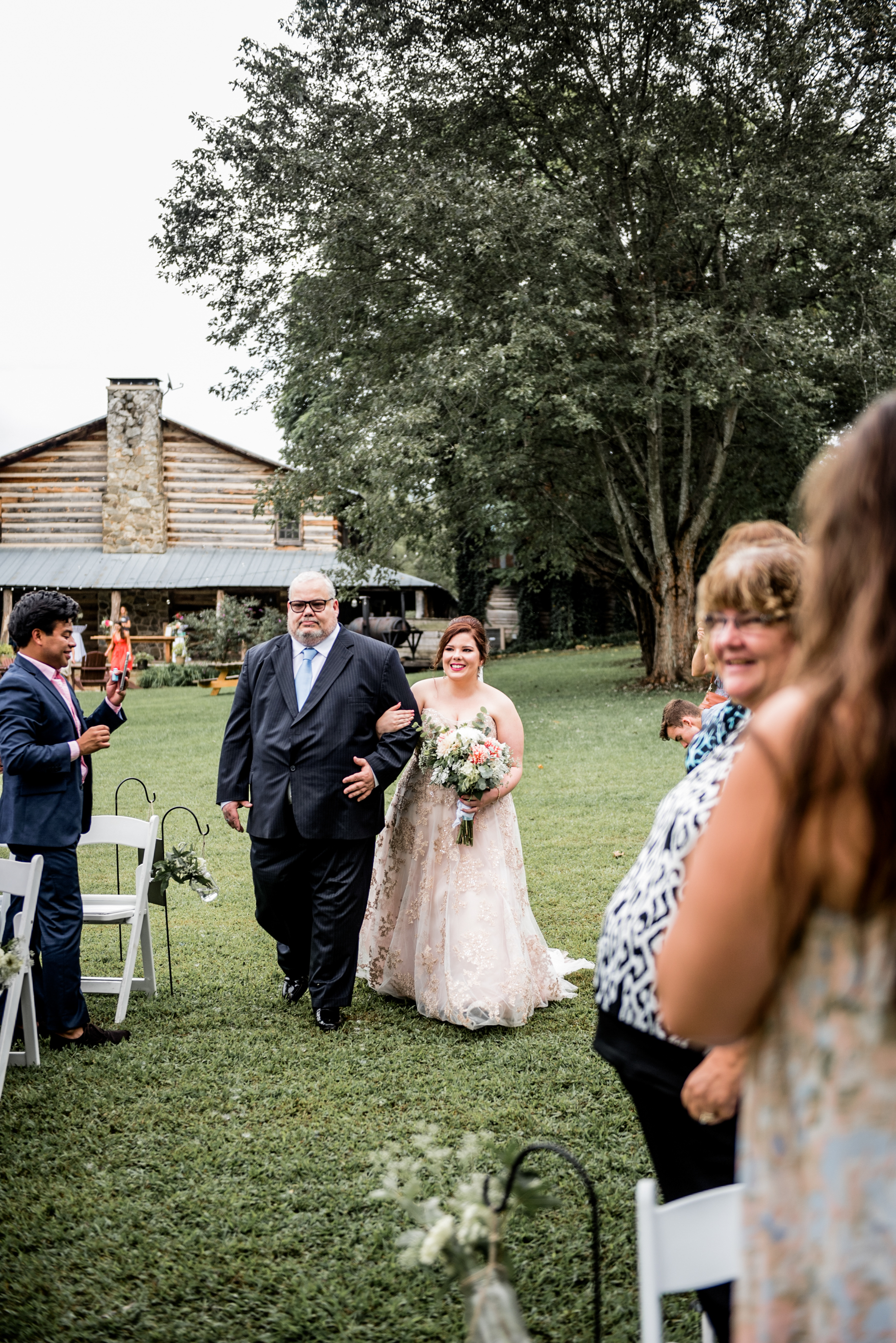 bride and father walk down aisle with rustic lodge in background