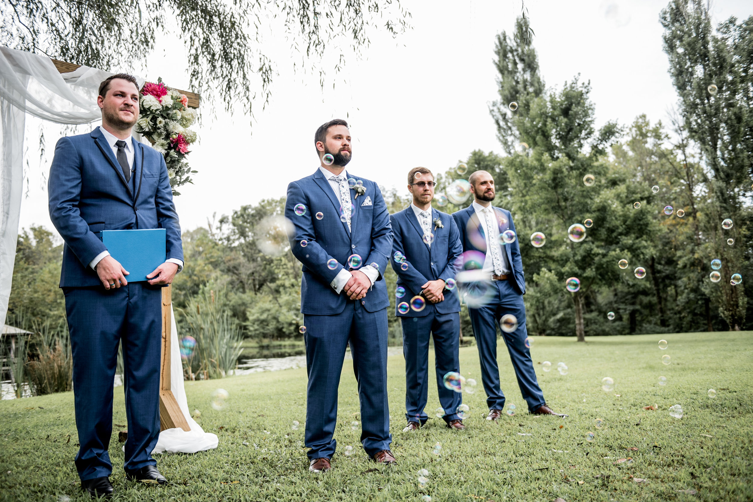 groom watches bride walk down aisle with bubbles