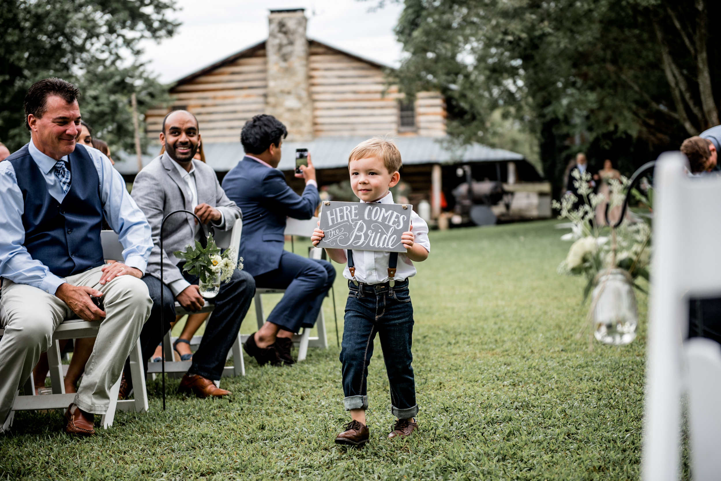 adorable ring bearer walks down aisle with here comes the bride sign