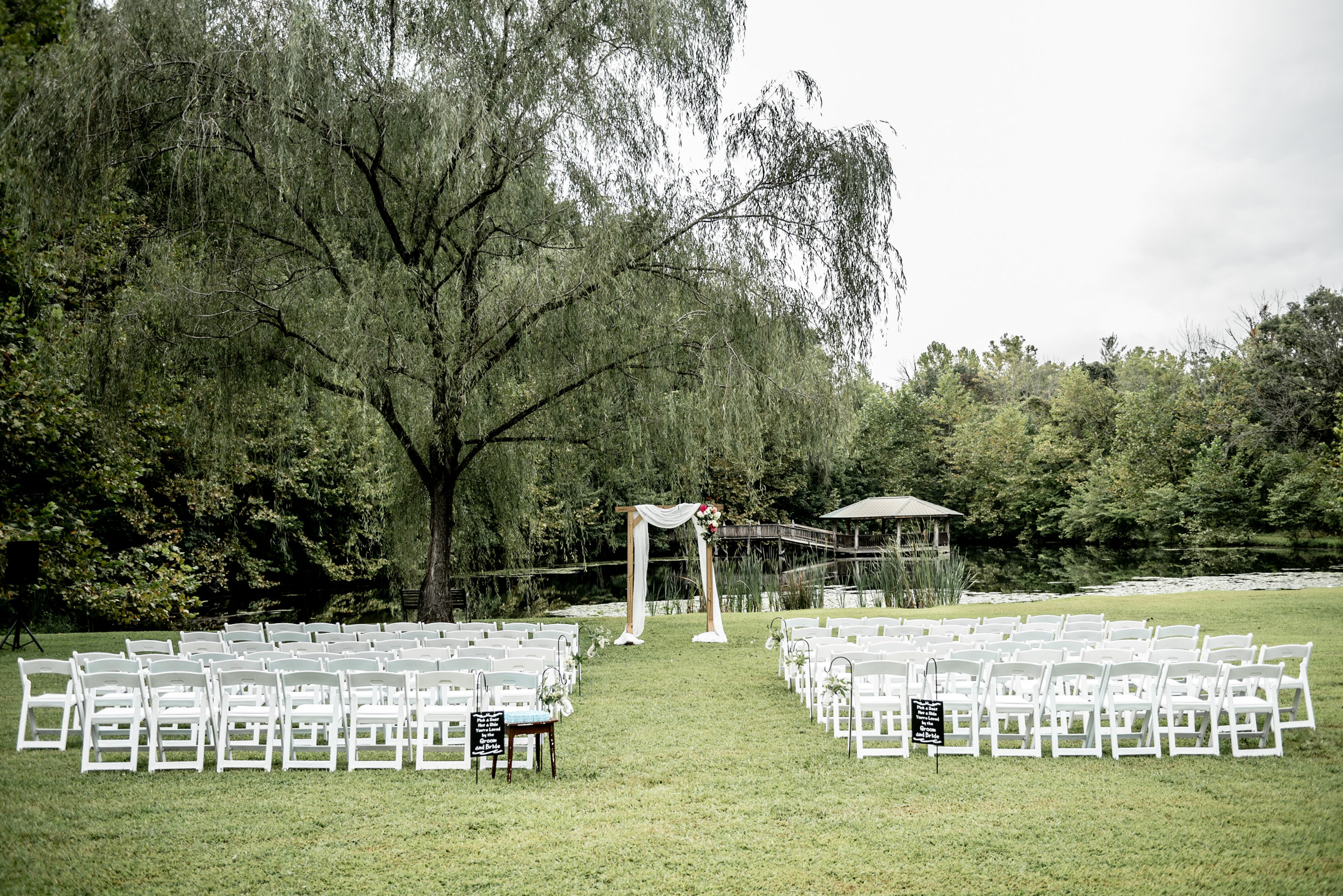 Romantic wedding ceremony under willow tree by pond