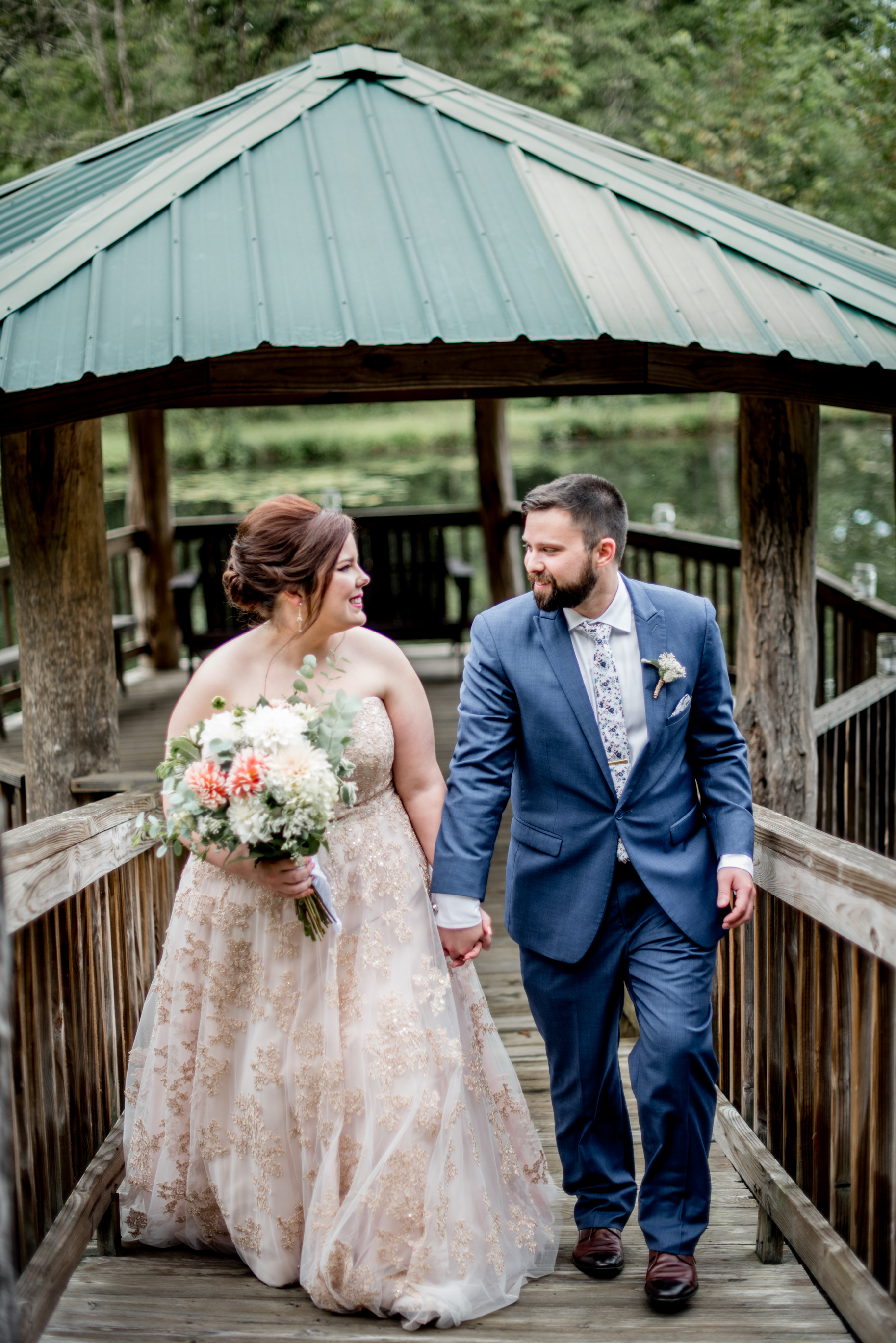 Bride and groom stroll along bridge over pond for romantic first look