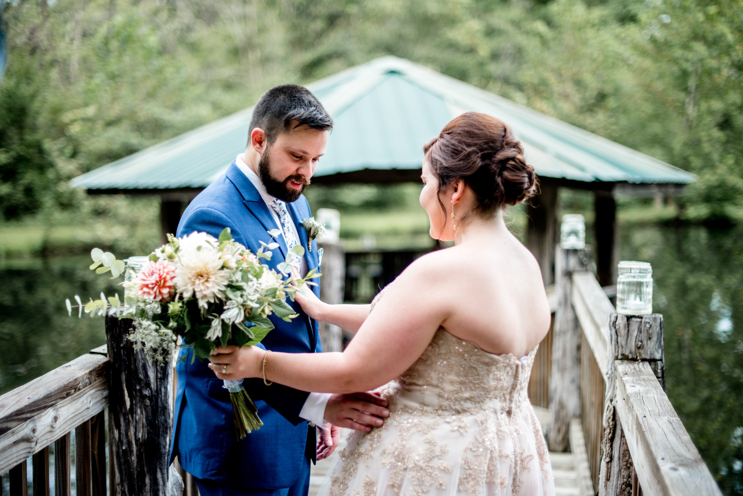 Romantic first look on scenic bridge over pond with rustic gazebo