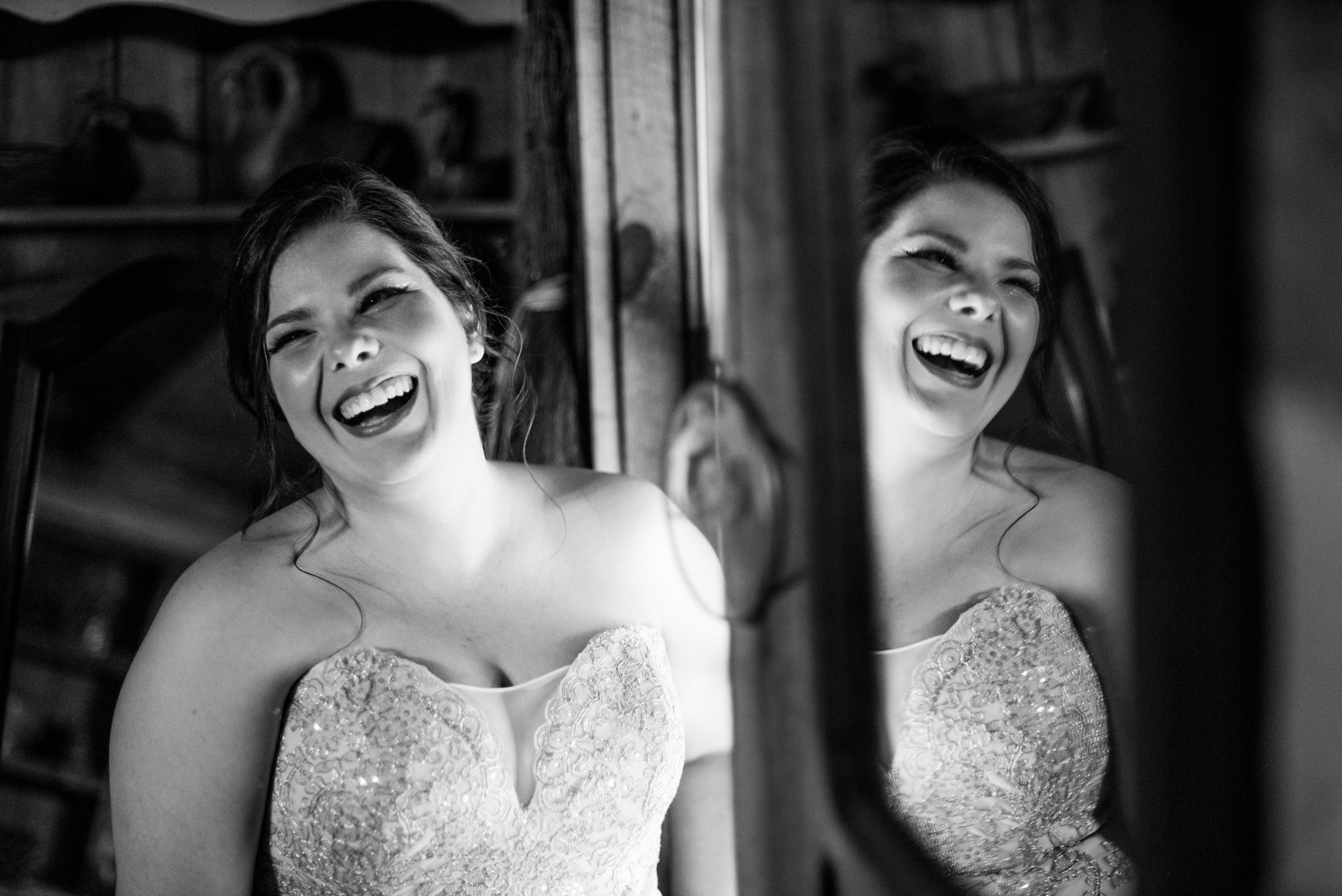Bride laughs while getting ready black & white