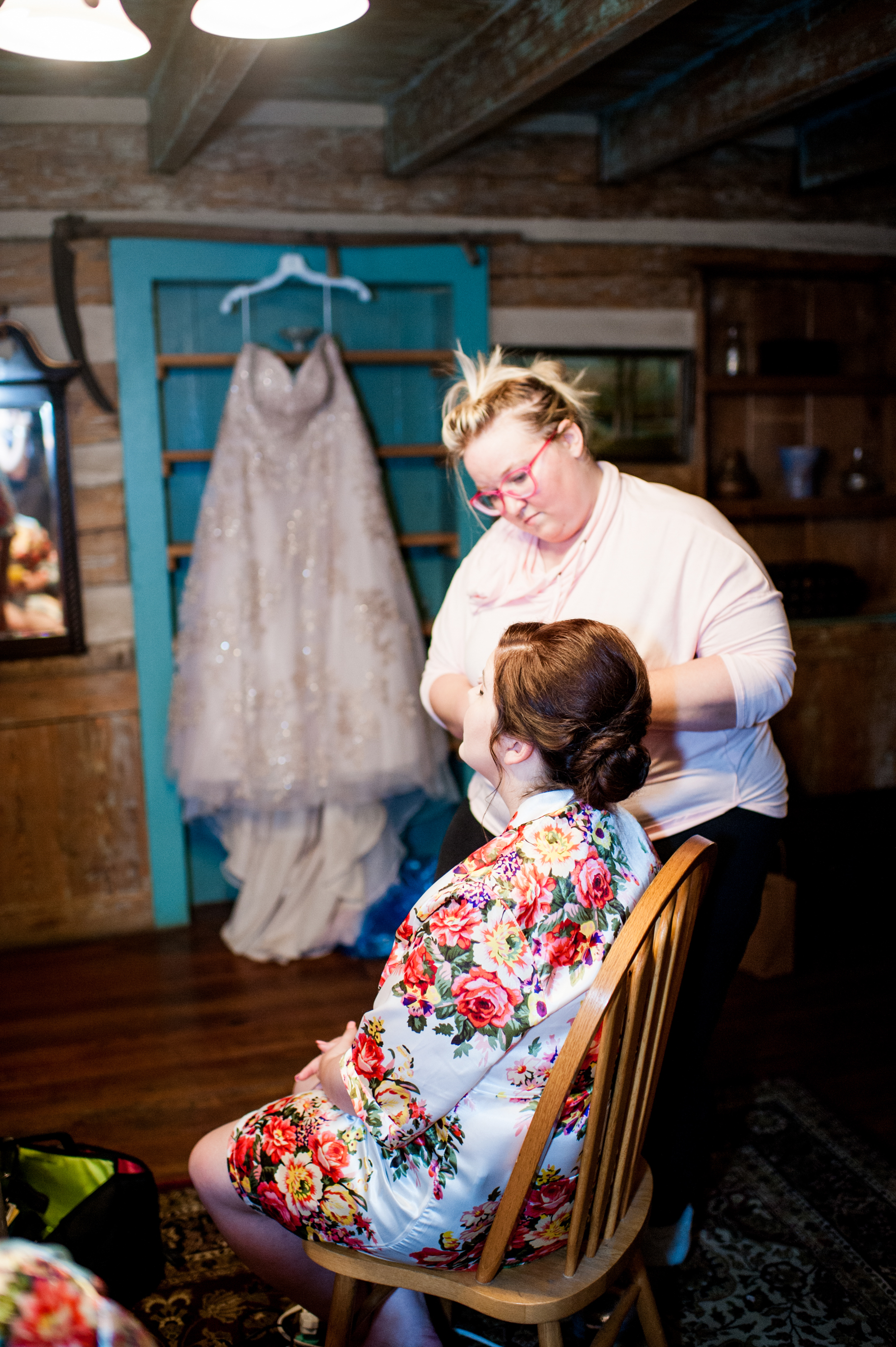 Bride gets makeup done in cabin with gown