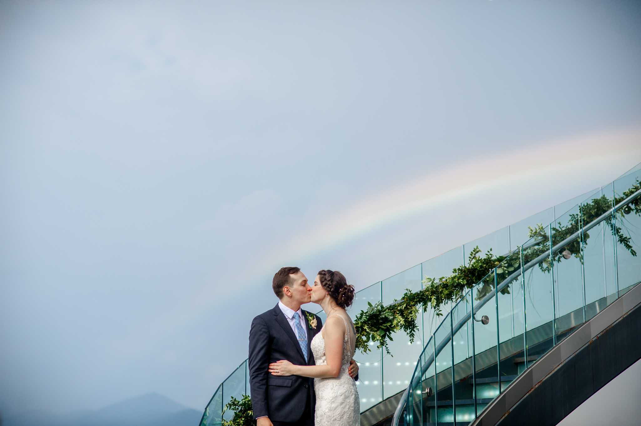 bride and groom share a kiss under a rainbow at downtown roanoke rooftop wedding