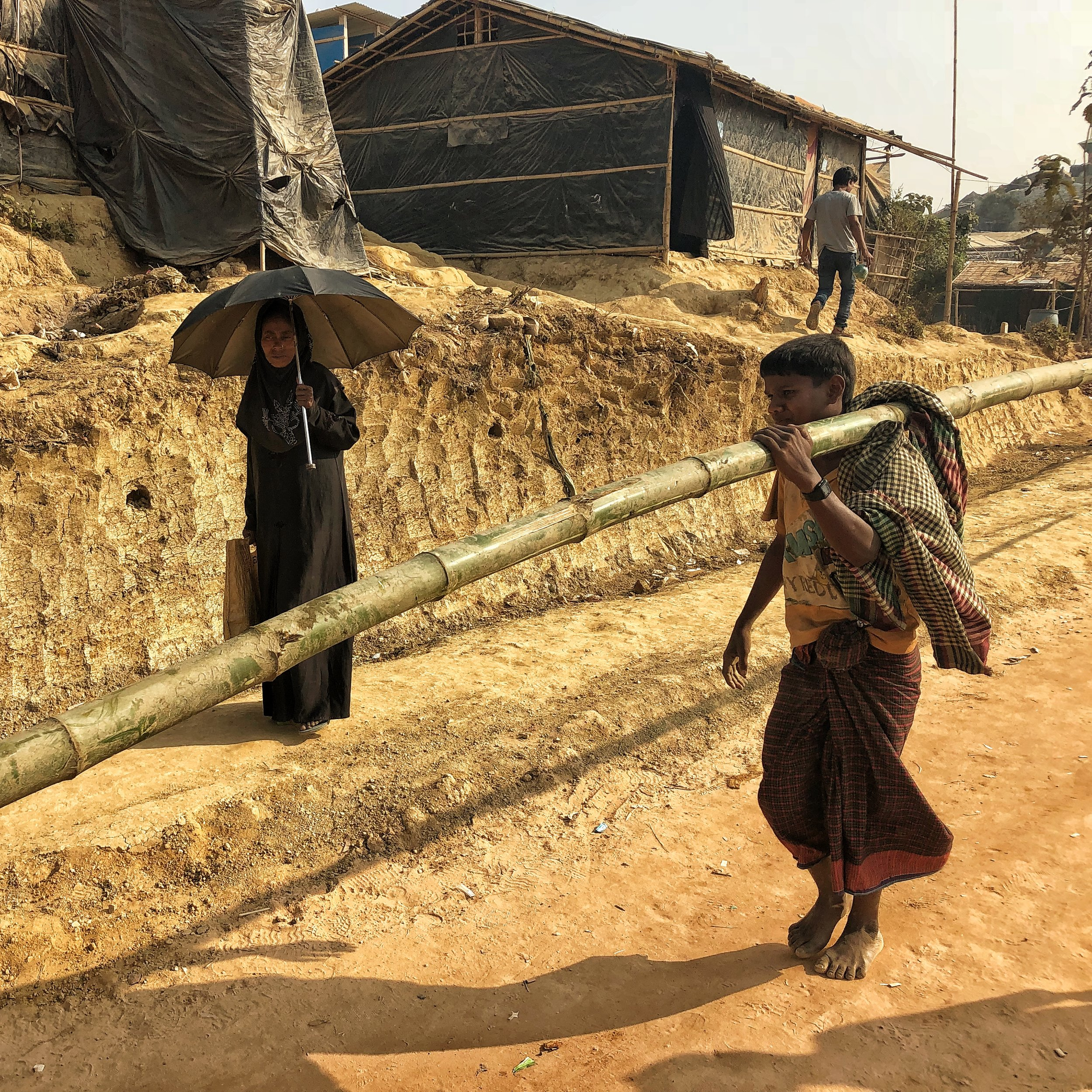 A man carries bamboo along a newly dug road in Tangkhali Refugee Camp