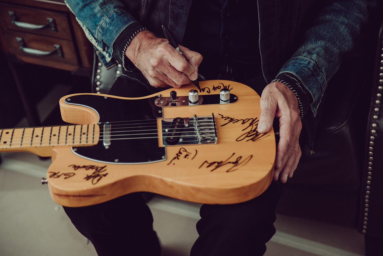 grand funk railroad lead singer signing guitar.jpg