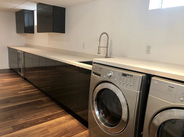 Laundry room in high gloss anthracite flat panel door with discreet edge pulls. Quartz countertops by @caesarstoneca  #high gloss #anthracite #cloudburstconcretecountertops #stainlessedgepulls