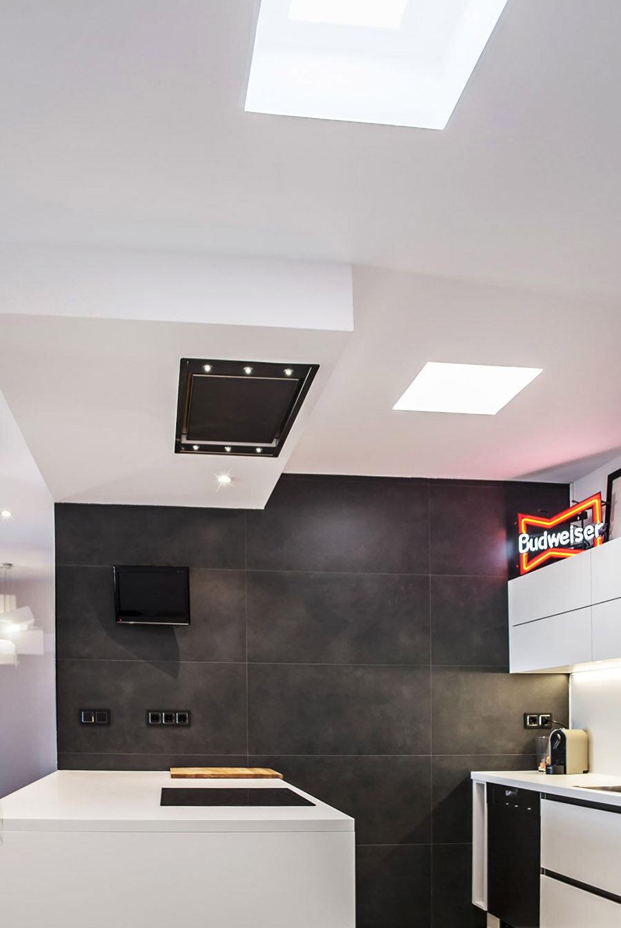 Vista de la cocina, con el espacio de la escalera al fondo y los lucernarios artificiales encendidos en el falso techo.