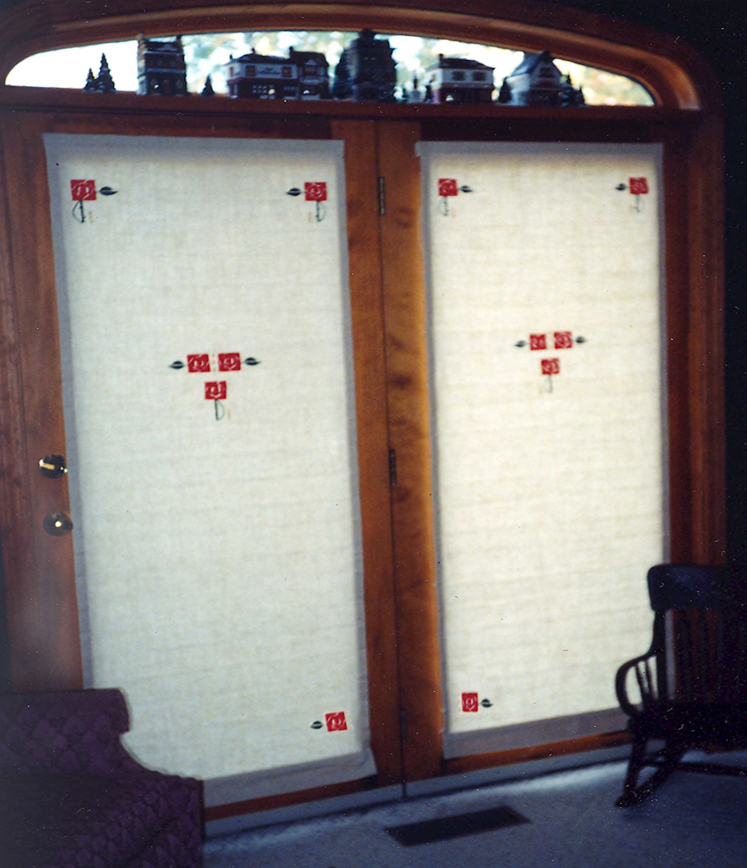 Shades pulled on a pair of doors. Only the top two Macintosh Rose appliques would show when the shade is raised.