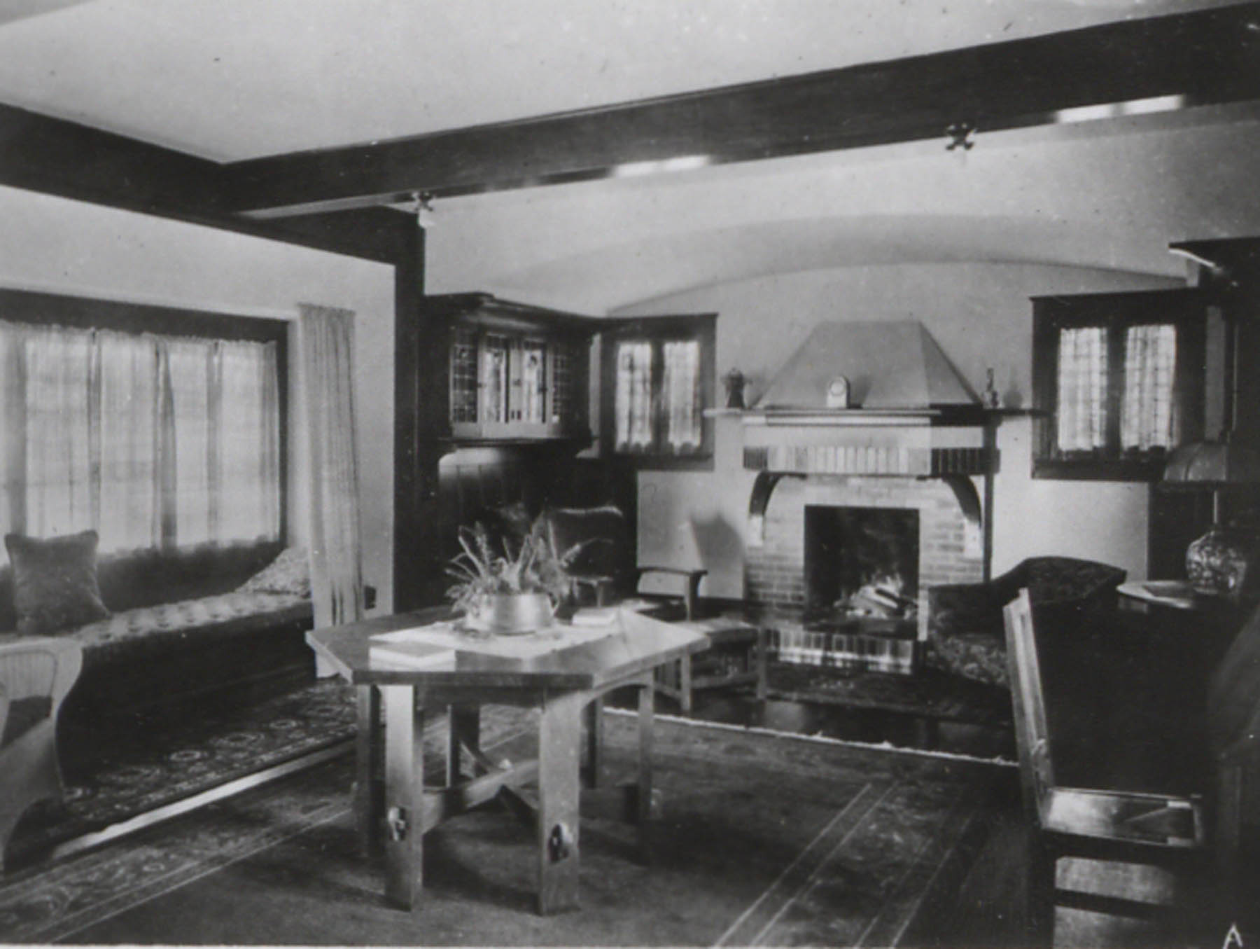 At left, a window seat with a box cushion can be seen in this vintage Arts & Crafts interior.