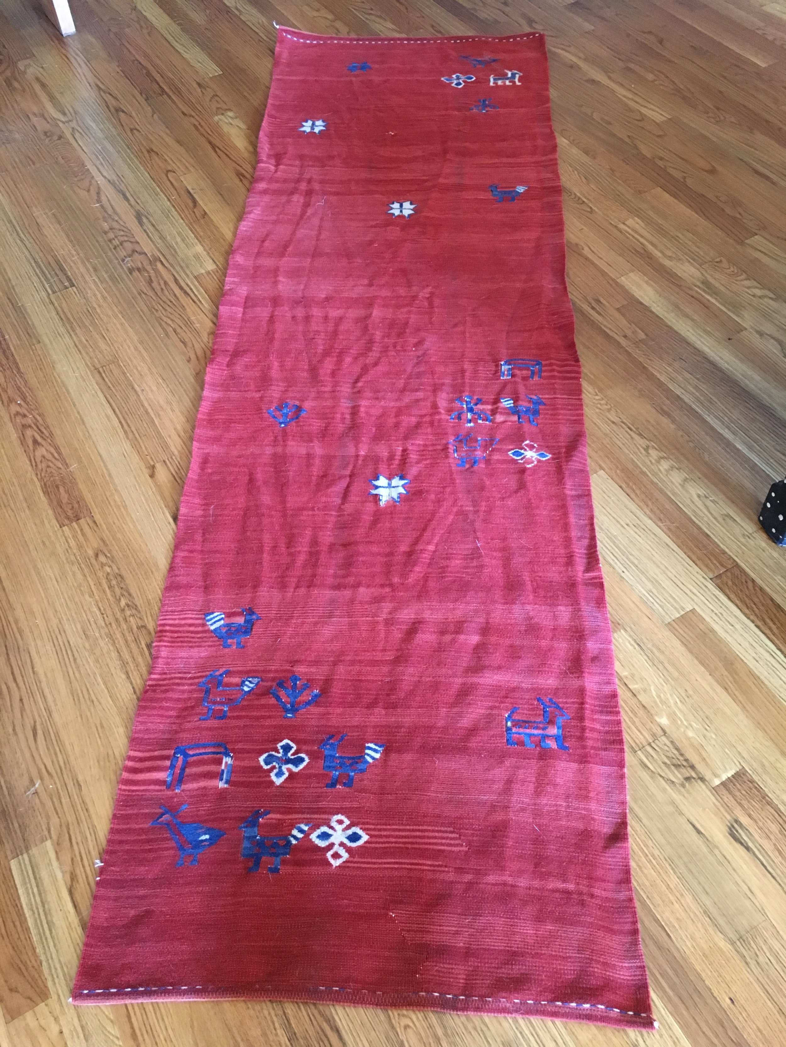 Wool has memory and the rug will flatten more as it dries. Do dry it flat if you can. Hanging over a rod as it dries can make a crease that is hard to get out. You CAN iron your rug. Spritz with a bit of water and use a pressing cloth.