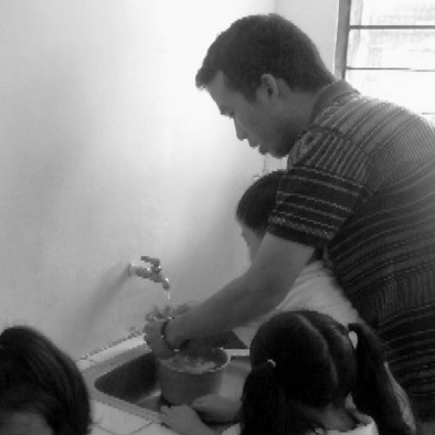 ADCC health worker demonstrating proper hand-washing techniques