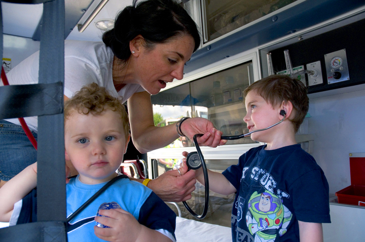 "Children learning about the activities that takes place inside an ambulance at ""Touch a Truck"" in Danvers, MA."